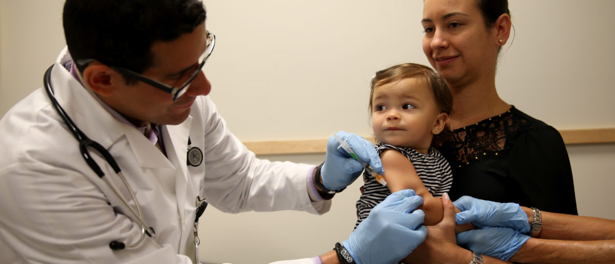 Daniela Chavarriaga holds her daughter, Emma Chavarriaga, as pediatrician Jose Rosa-Olivares, M.D. administers a measles vaccination ... (Photo by Joe Raedle/Getty Images)