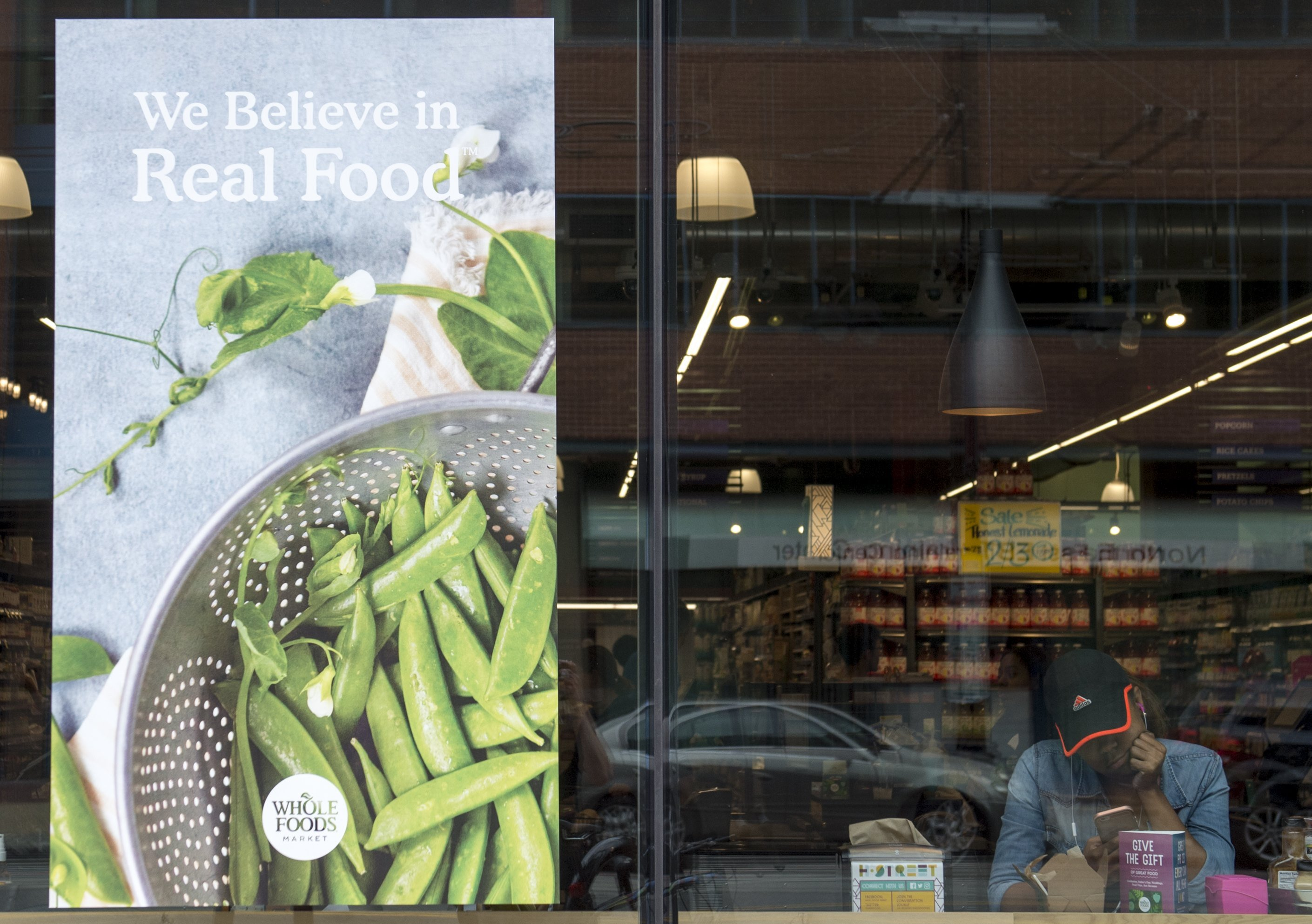 A woman looks at her phone at a Whole Foods Market in Washington, DC, June 16, 2017, following the announcement that Amazon would purchase the supermarket chain for $13.7 billion. (SAUL LOEB/AFP/Getty Images)