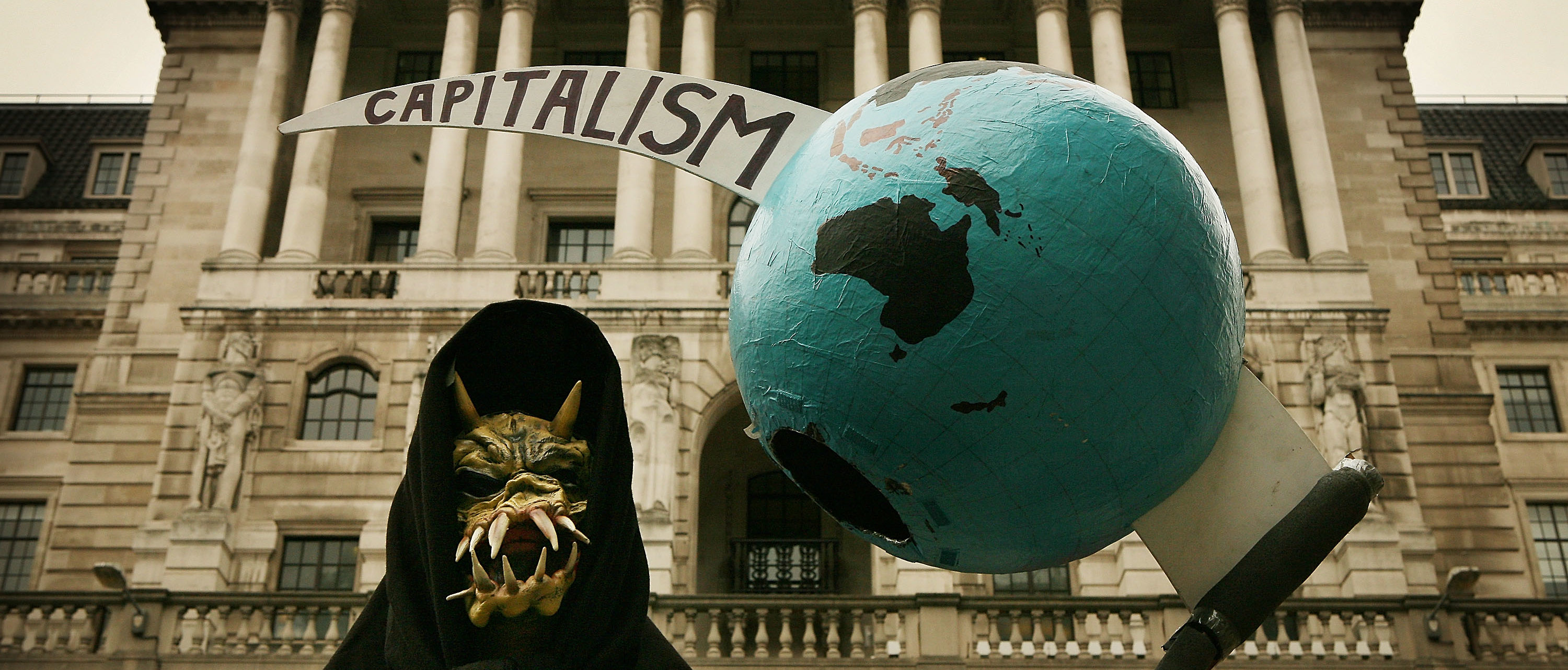 LONDON - OCTOBER 13: A grim reaper figure holds a globe pierced by the scythe of capitalism in front of the Bank of England during a protest on October 13, 2008 in London. The UK Government has announced a £37 billion bail out of three retail banks. (Photo by Peter Macdiarmid/Getty Images)