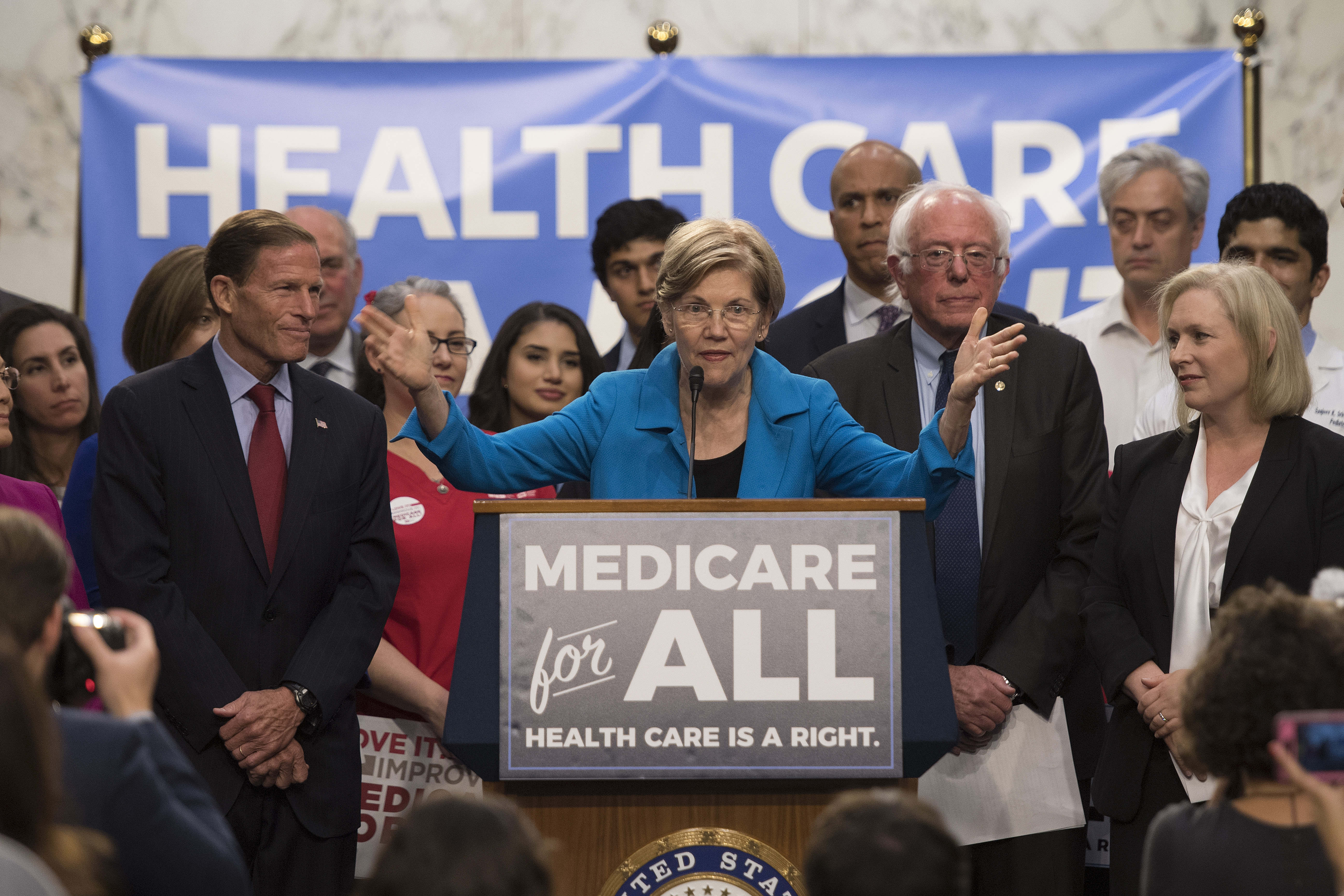 US Senator Elizabeth Warren (C), Democrat from Massachusetts, speaks with US Senator Bernie Sanders (2nd R), Independent from Vermont, as they discusses Medicare for All legislation on Capitol Hill in Washington, DC, on September 13, 2017. (JIM WATSON/AFP/Getty Images)