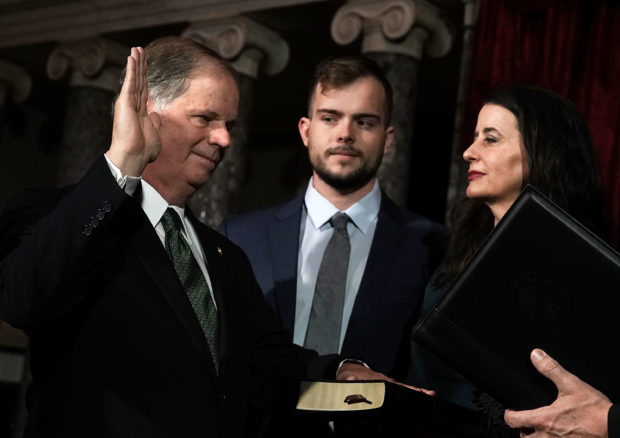 WASHINGTON, DC - JANUARY 03: U.S. Sen. Doug Jones (D-AL) (L) participates in a mock swearing-in ceremony as Jones' wife Louise (R) and son Carson (2nd L) look on at the Old Senate Chamber of the U.S. Capitol January 3, 2018 in Washington, DC. Jones is the first Democratic senator from Alabama in more than two decades. He defeated Roy Moore leaving Republicans with a 51-49 majority in the U.S. Senate. (Photo by Alex Wong/Getty Images)
