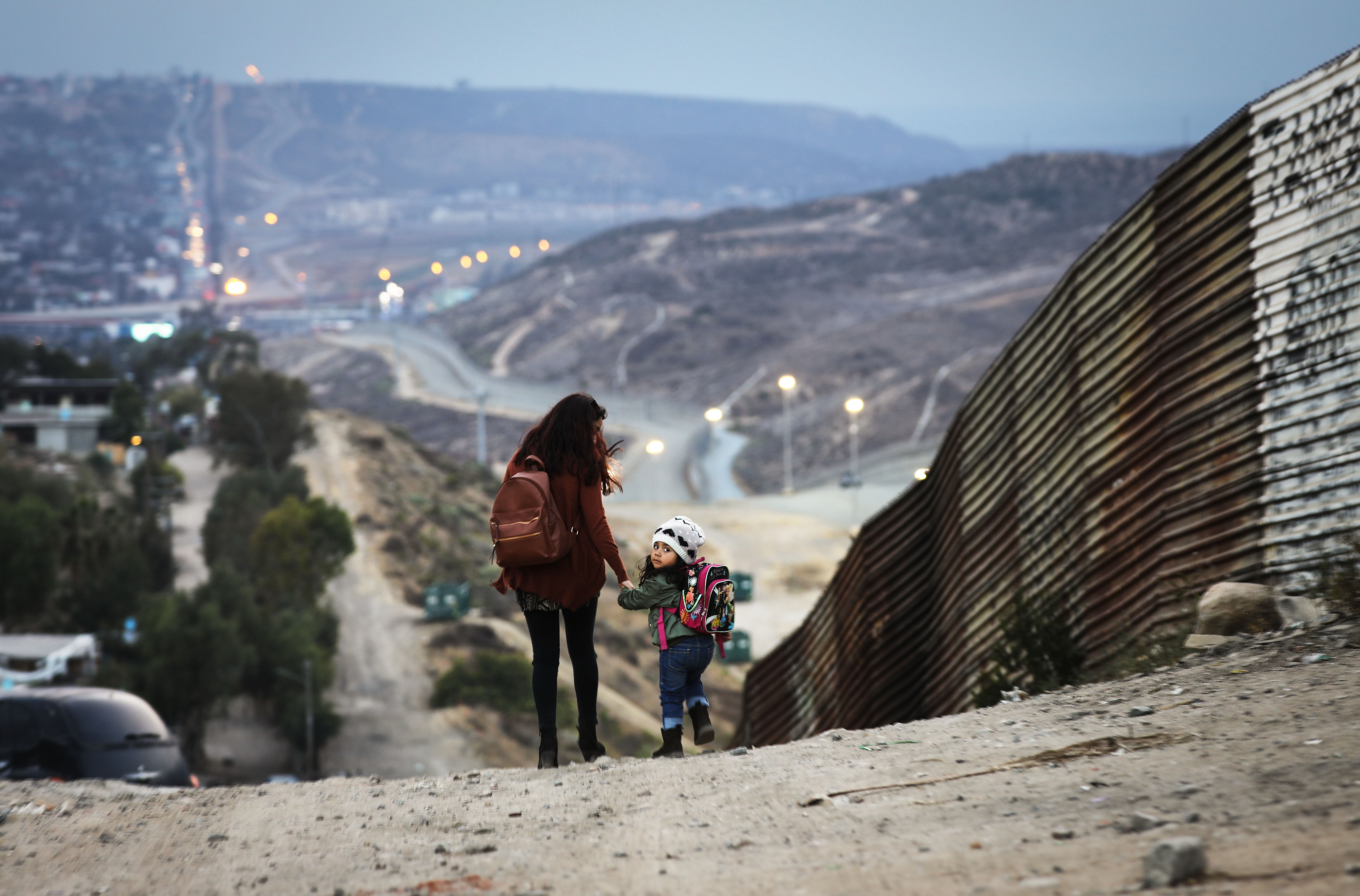 Local residents walk along the Mexico side of the U.S.-Mexico border on June 19, 2018 in Tijuana, Mexico ... (Photo by Mario Tama/Getty Images)