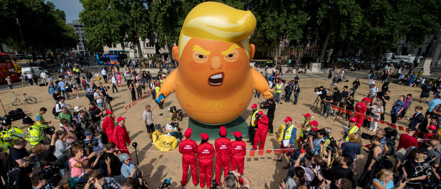 LONDON, UNITED KINGDOM - JULY 13: Demonstrators raise a six meter high effigy of Donald Trump, being dubbed the 'Trump Baby', in Parliament Square in protest against the U.S. President's current visit to the United Kingdom on July 13, 2018 in London, United Kingdom. The President of the United States and First Lady, Melania Trump, touched down yesterday in the UK on Air Force One for their first official visit. Today the President will visit Prime Minister Theresa May at Chequers and take tea with the Queen at Windsor Castle. (Photo by Chris J Ratcliffe/Getty Images)