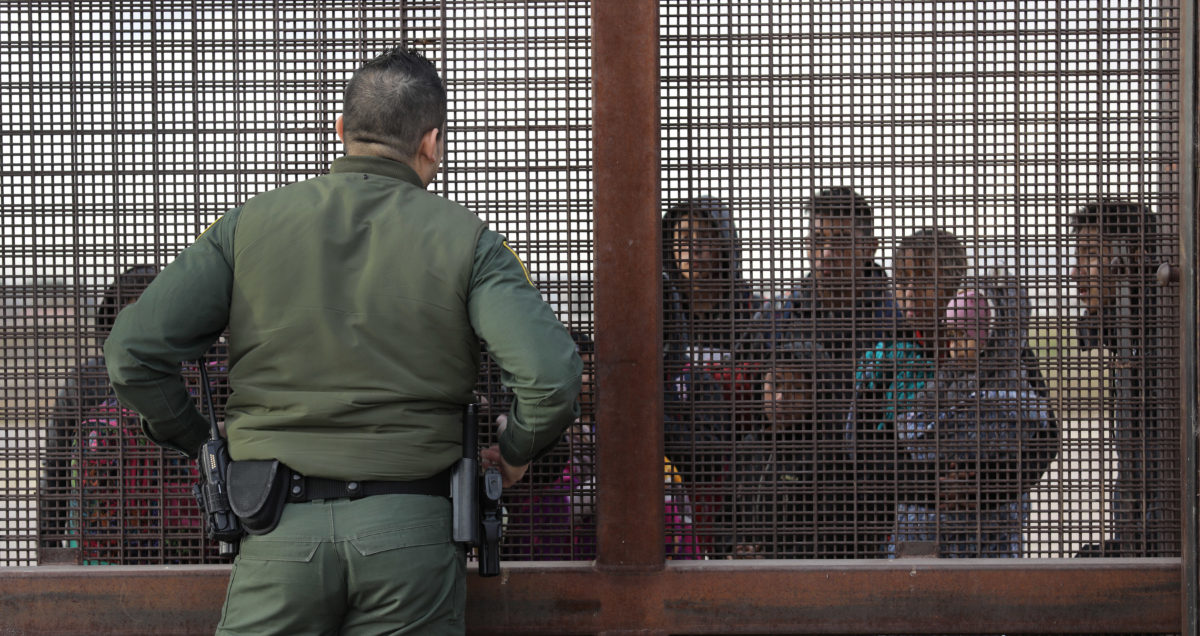 EL PASO, TEXAS - FEBRUARY 01: A U.S. Border Patrol agent speaks with Central American immigrants at the border fence after they crossed the Rio Grande from Mexico on February 01, 2019 in El Paso, Texas. The migrants, who said they were from Guatemala, turned themselves in to U.S. Border Patrol agents, seeking asylum in the United States. (Photo by John Moore/Getty Images)