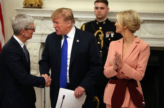 U.S. President Donald Trump shakes hands with Apple CEO Tim Cook as White House senior advisor Ivanka Trump (R) looks on, during an American Workforce Policy Advisory Board meeting in the White House State Dining Room in Washington, U.S., March 6, 2019. REUTERS/Leah Millis