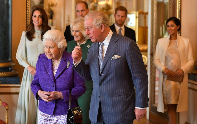 Britain's Prince Charles, Prince of Wales (C) walks with his mother Britain's Queen Elizabeth II (2L), and his wife Britain's Camilla, Duchess of Cornwall (3L), and his sons and their wives, Britain's Prince William, Duke of Cambridge (4L) and Britain's Catherine, Duchess of Cambridge (L), and Britain's Prince Harry, Duke of Sussex, (2R) and Meghan, Duchess of Sussex (R) during a reception to mark the 50th Anniversary of the investiture of The Prince of Wales at Buckingham Palace in London on March 5, 2019. (Photo credit: DOMINIC LIPINSKI/AFP/Getty Images)