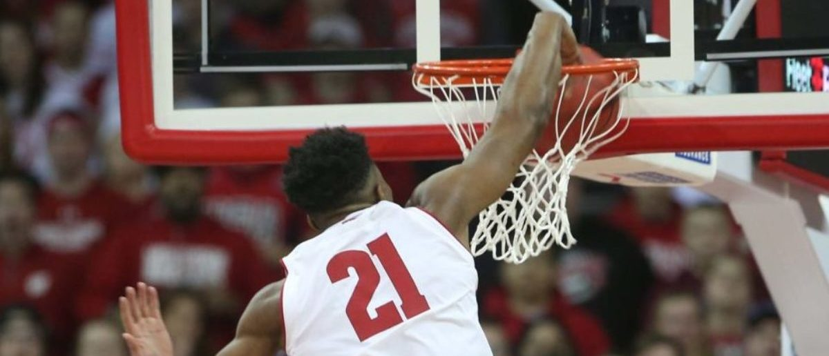Mar 7, 2019; Madison, WI, USA; Wisconsin Badgers guard Khalil Iverson (21) dunks the ball as Iowa Hawkeyes guard Joe Wieskamp (10) looks on during the first half at the Kohl Center. Mandatory (Credit: Mary Langenfeld-USA TODAY Sports - via Reuters)