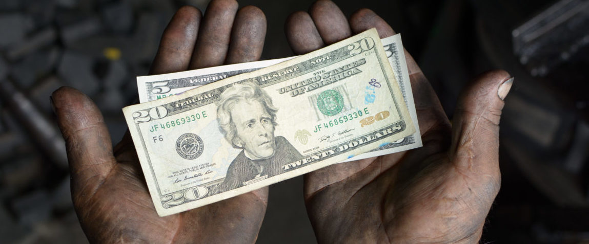 Worker hands covered with oil holding money. Shutterstock