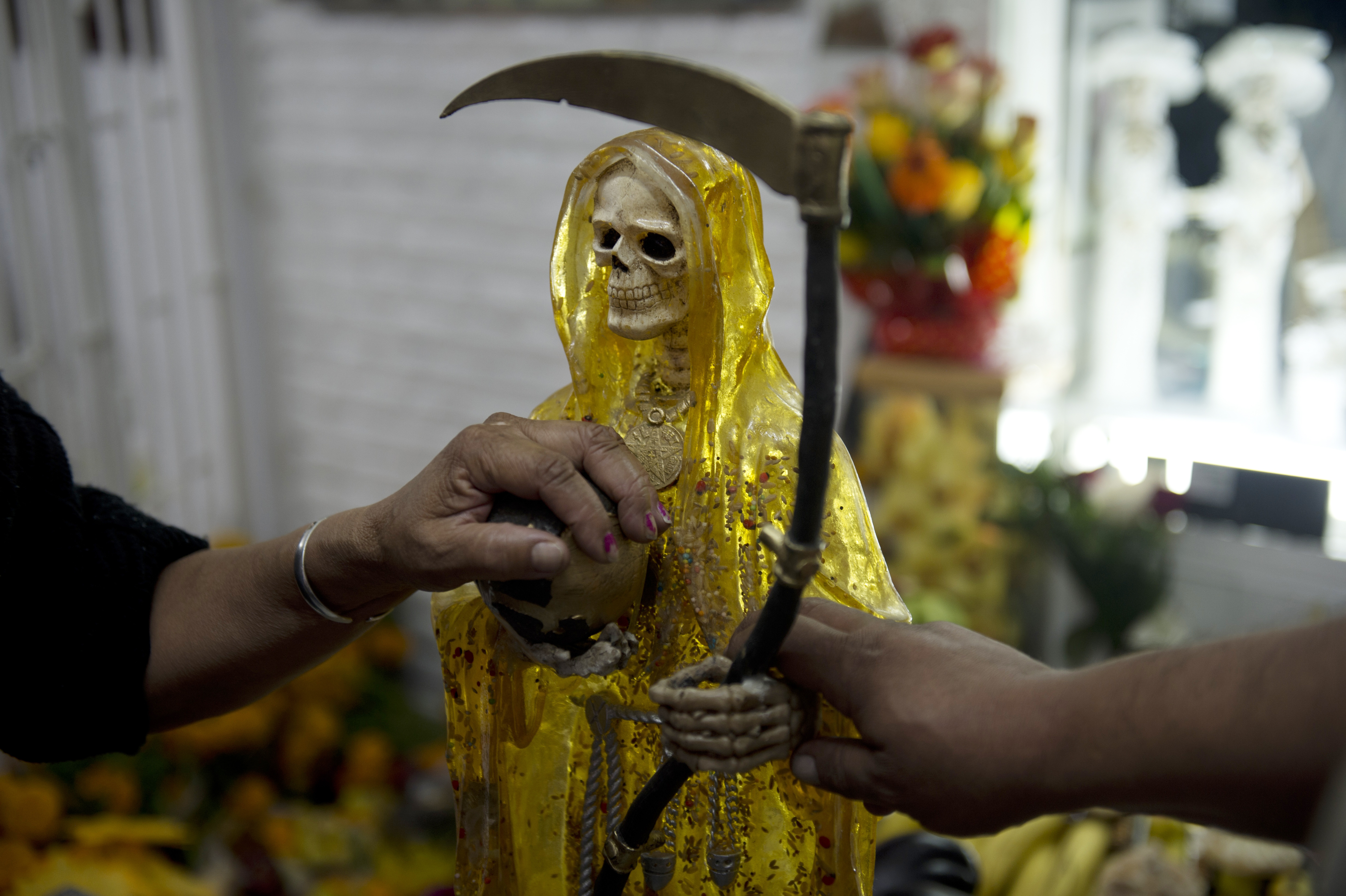 Devotees touch the figures of Santa Muerte (Saint of Death) before the central altar asking for favors during the main celebration in the market of one of the most dangerous neighborhoods, known as Tepito in Mexico City, on November 1, 2012. (YURI CORTEZ/AFP/Getty Images)