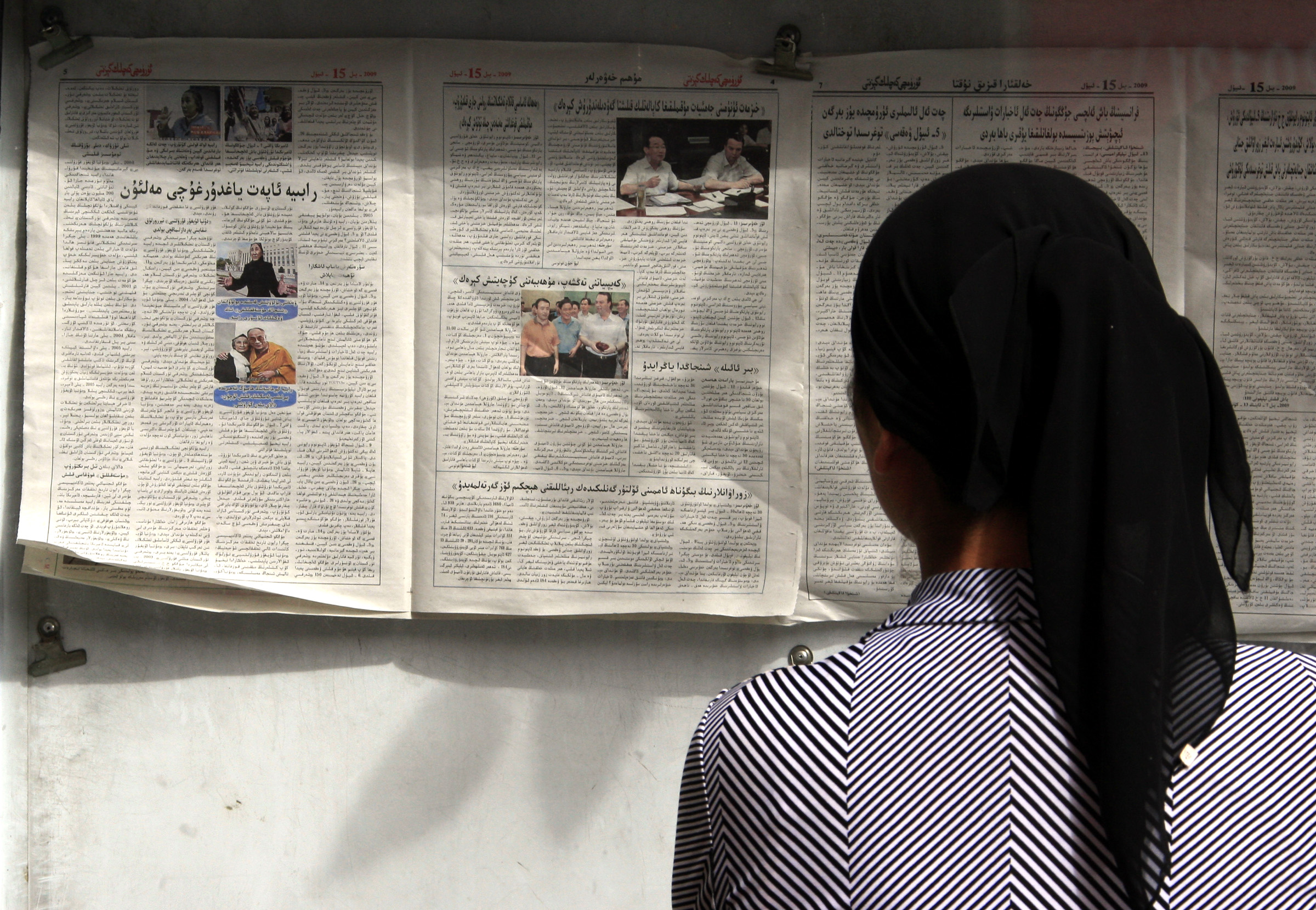 An ethnic Uighur women reads a newspaper on display on a notice board in the city of Urumqi in China's Xinjiang Autonomous Region/ REUTERS/David Gray
