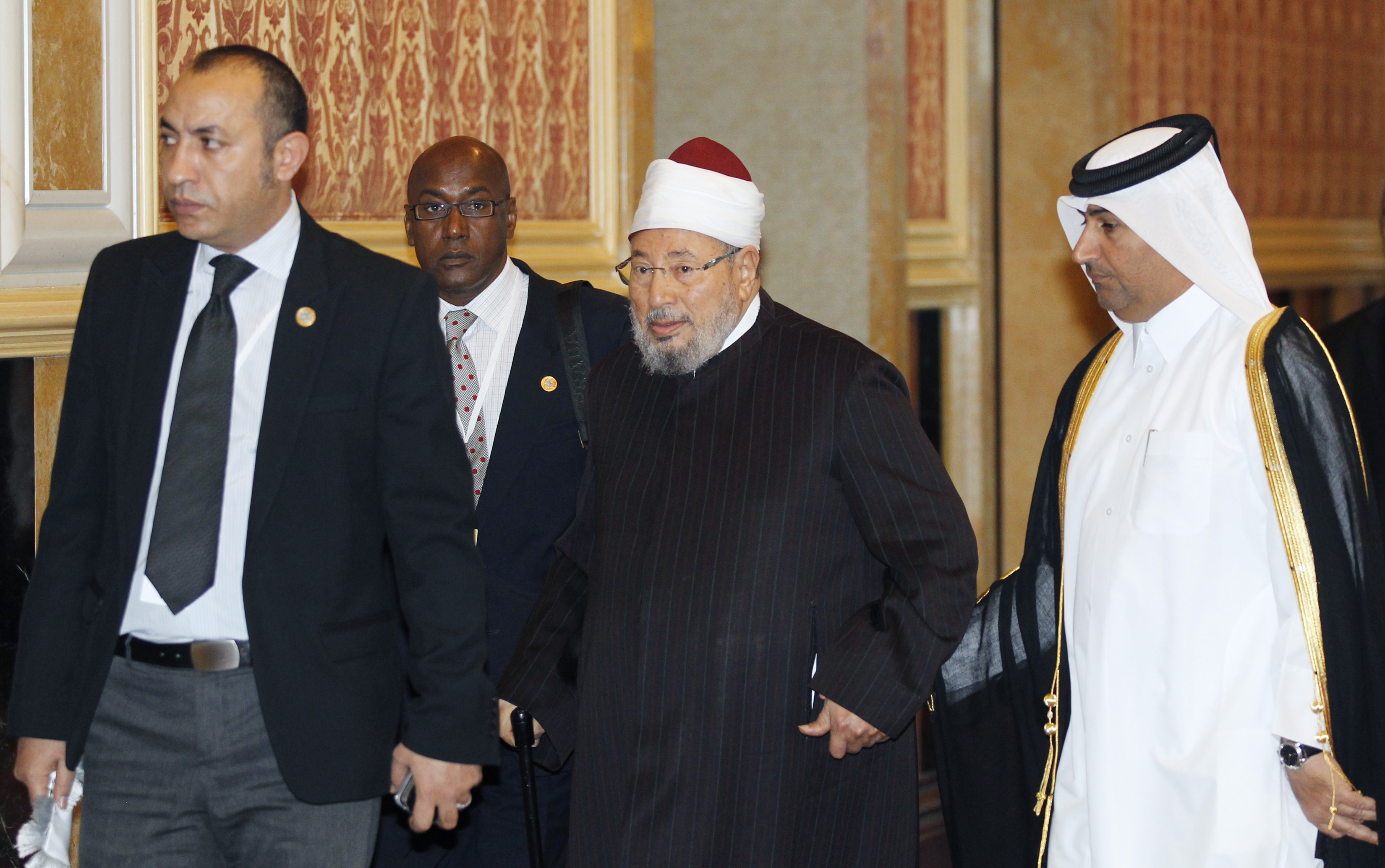 Sheikh Yusuf al-Qaradawi (C) arrives at the opening of the International Conference on Jerusalem in Doha February 26, 2012. (Photo by REUTERS/Mohammed Dabbous)