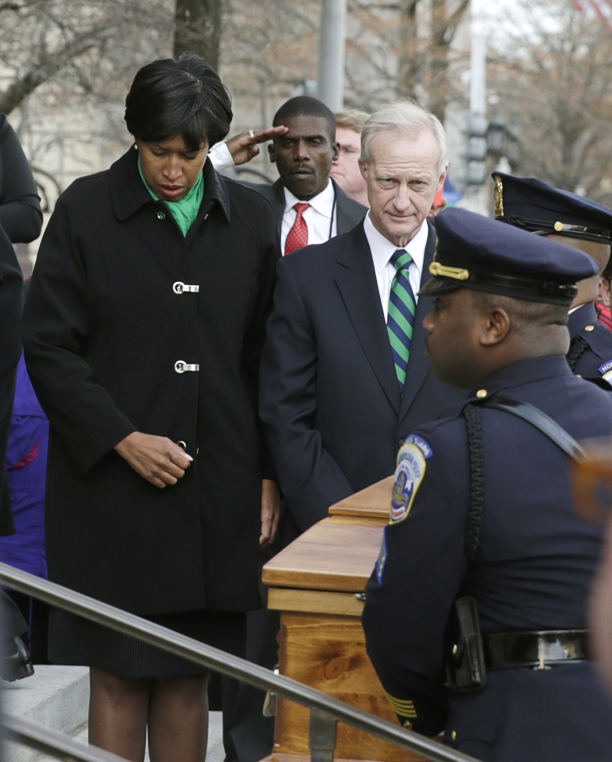 Incoming Washington, D.C. Mayor Muriel Bowser (L) and City Councilmember Jack Evans (R) bow their heads as former Washington D.C. Mayor and city councilmember Marion Barry's casket arrives at the Wilson Building in Washington December 4, 2014. REUTERS/Gary Cameron