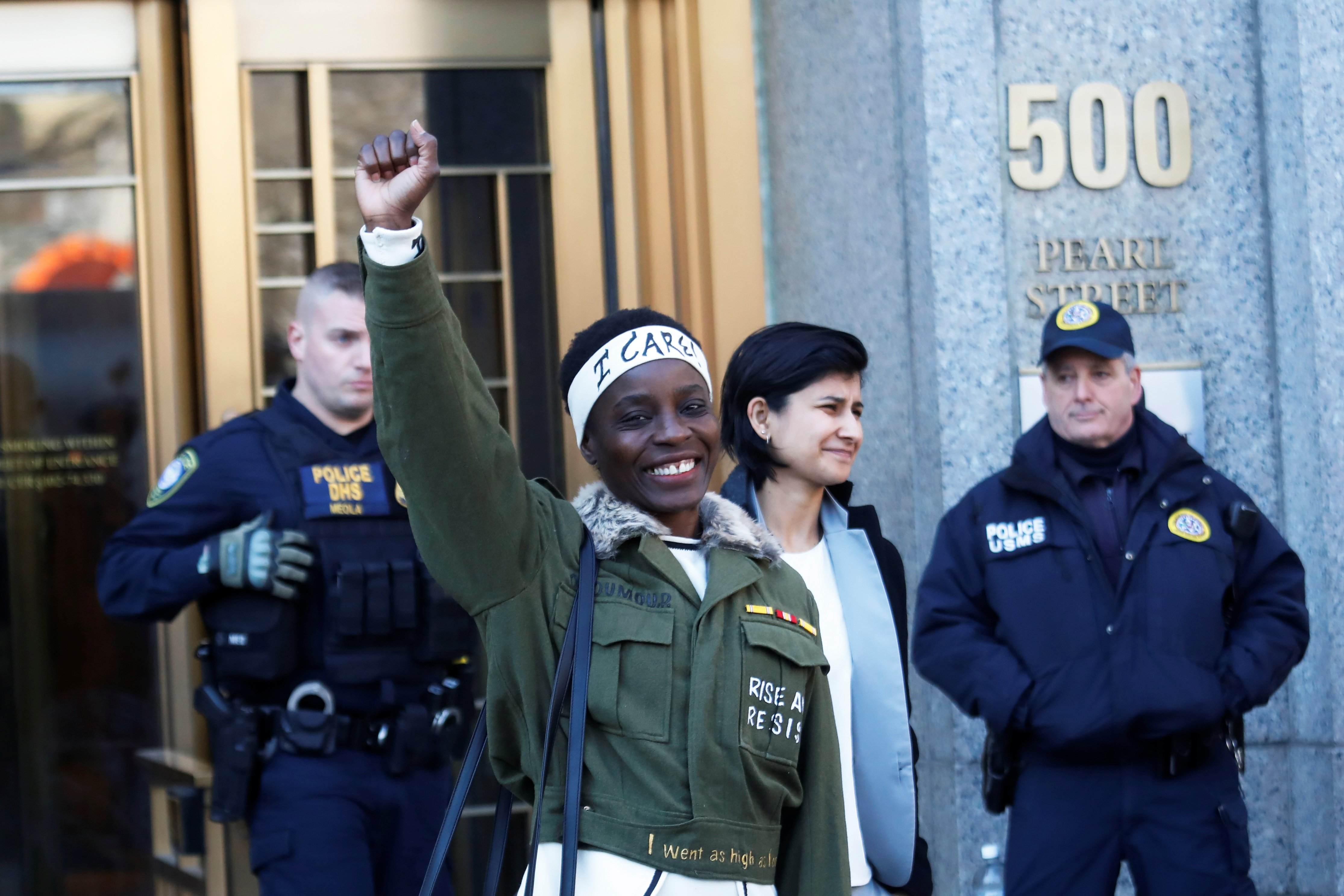 Therese Patricia Okoumou raises her fist after her sentencing for conviction on attempted scaling of the Statue of Liberty to protest the U.S. immigration policy, outside a federal court in New York, U.S., March 19, 2019. REUTERS/Shannon Stapleton