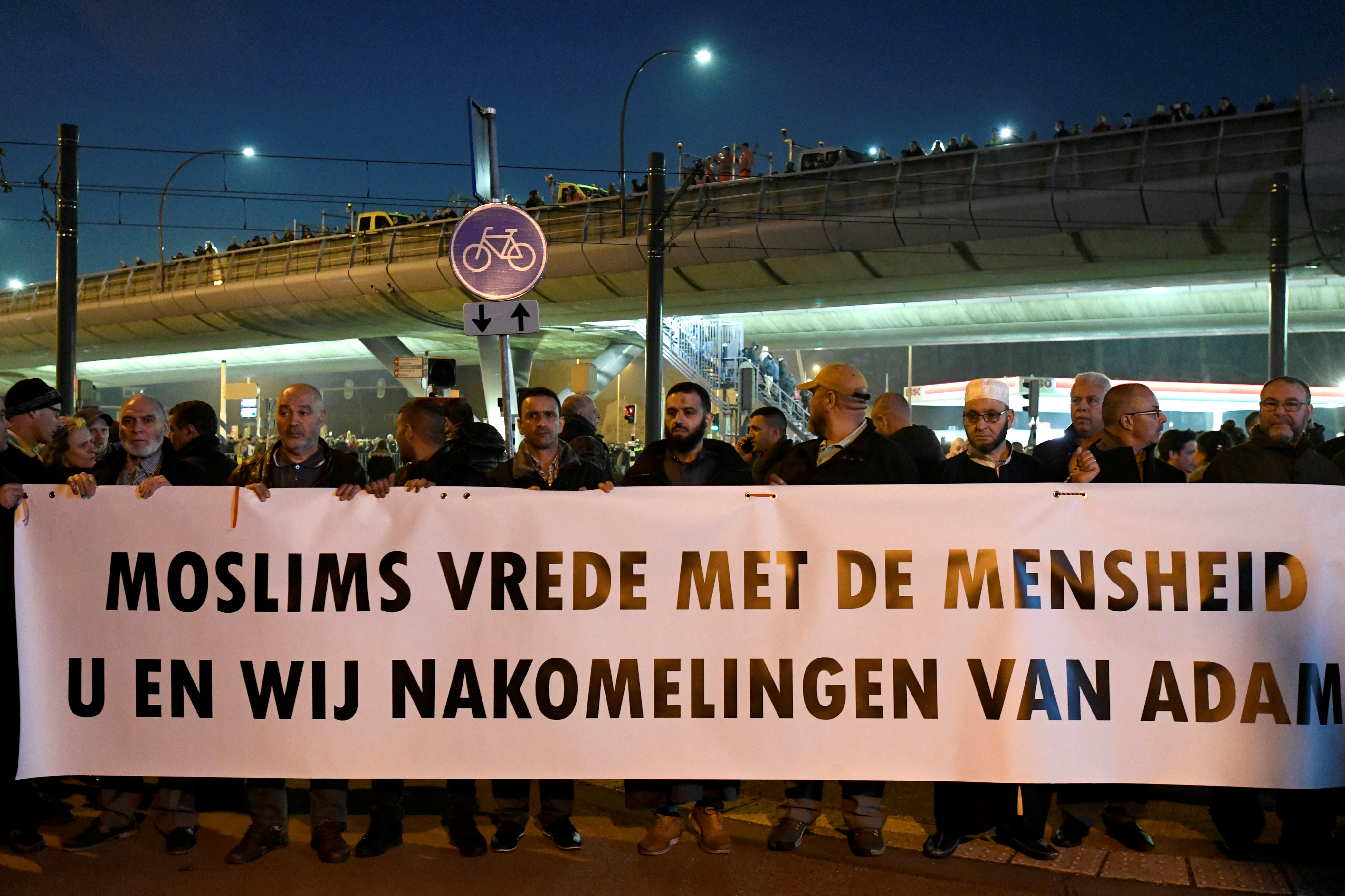 "People attend a silent march in Utrecht in honour of the people wounded or killed in an attack on a tram on Monday, in Utrecht, Netherlands March 22, 2019. The banner reads: ""Muslims peace with humanity. You and us descendants of Adam"" REUTERS/Piroschka Van De Wouw"