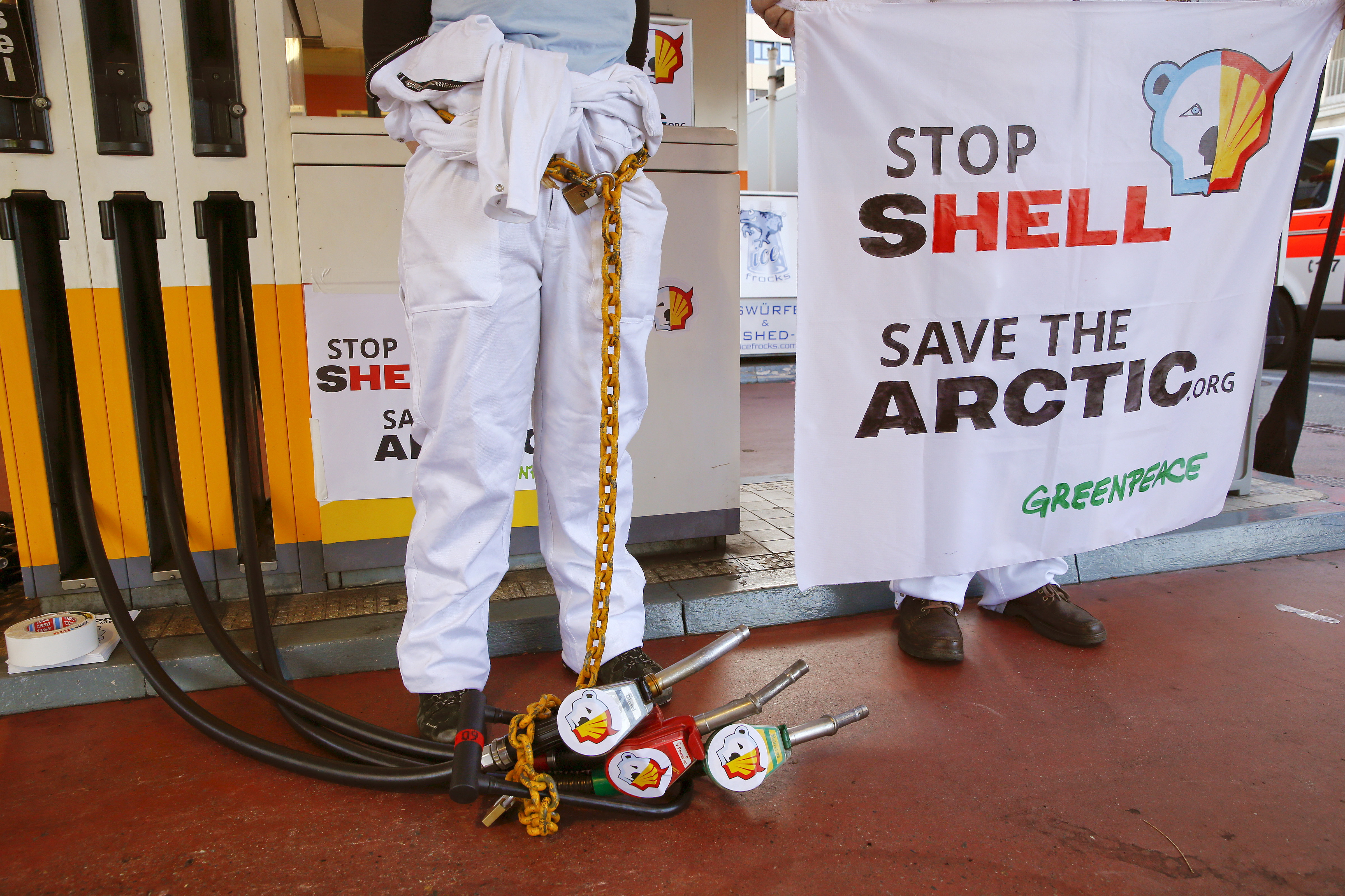 A member of Greenpeace is chained to a gas pump at a Shell gas station during a protest in Zurich