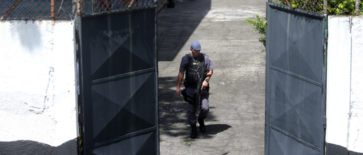 A policeman is seen in the entrance of the Raul Brasil school after a shooting in Suzano, Sao Paulo state, Brazil March 13, 2019. (REUTERS/Amanda Perobelli)