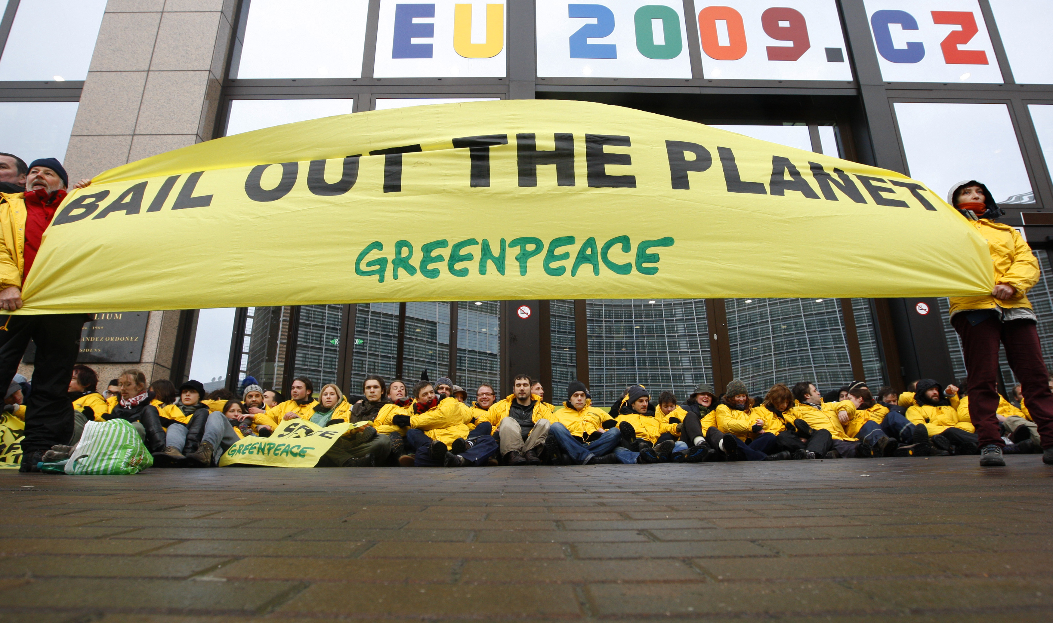 Greenpeace activists bar the entry to European Union headquarters in Brussels during a EU finance ministers meeting