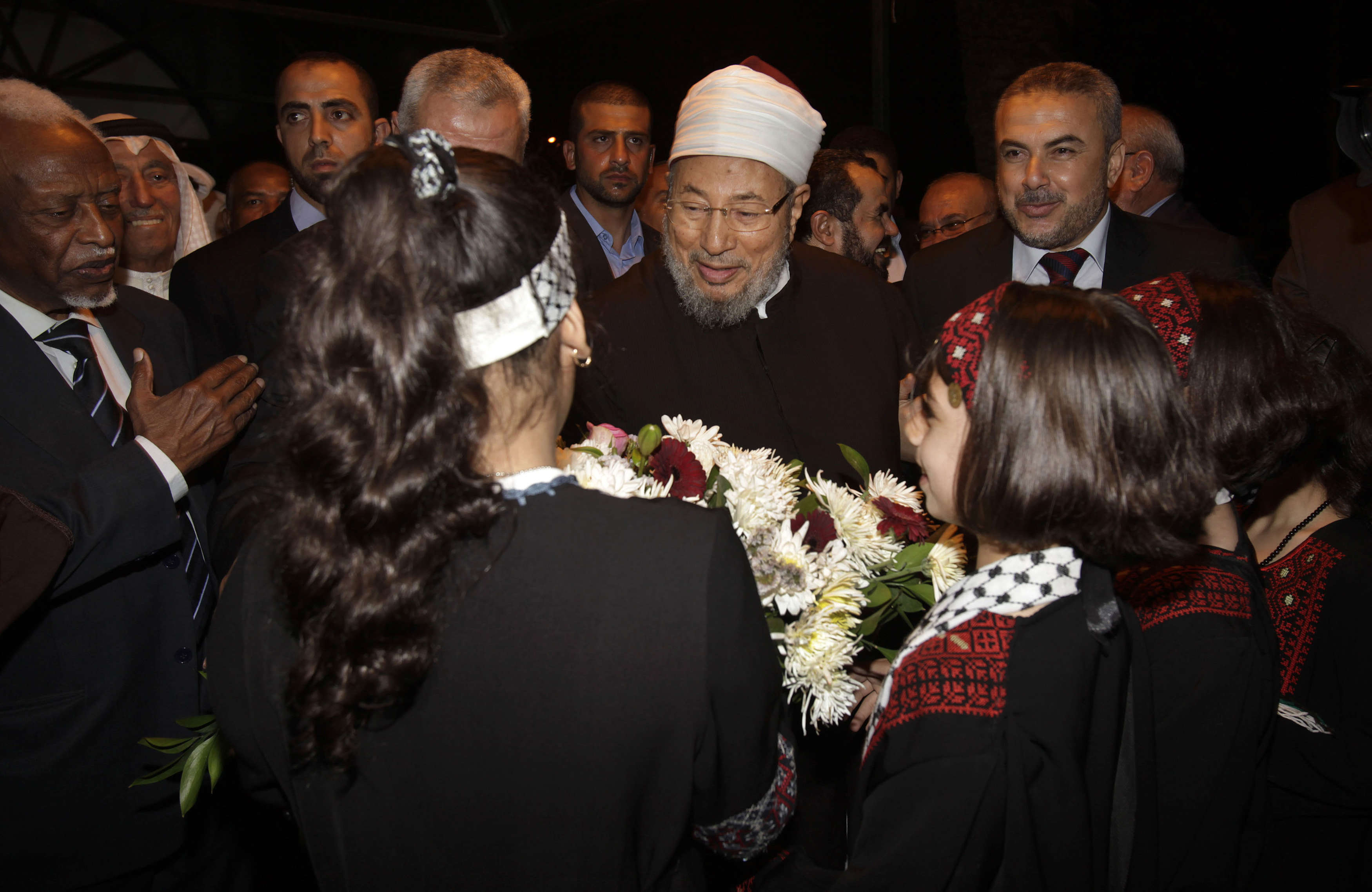 Egyptian Cleric and chairman of the International Union of Muslim Scholars Sheikh Yusuf al-Qaradawi receives flowers from Palestinian girls upon al-Qaradawi's arrival at Rafah Crossing in the southern Gaza Strip May 8, 2013. (Photo by REUTERS/Ibraheem Abu Mustafa)