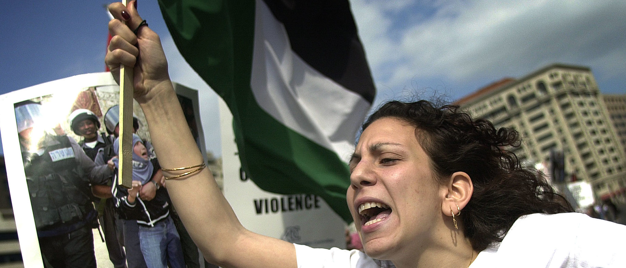"""Palestinian supporter Zeina Ashrawi, of the Students for Justice in Palestine Society of George Mason University, shouts in protest of Israel's occupation of Palesine while at a mass rally for the """"End the occupation, end the violence"""" demonstration on Freedom Plaza in Washington, DC, 30 March 2002. Israeli and Palestinian forces fought pitched street battles in the West Bank town of Ramallah 30 March as the siege of Yasser Arafat went into a second day with the UN Security Council calling for an Israeli withdrawal. AFP PHOTO/Jim WATSON (Photo credit should read JIM WATSON/AFP/Getty Images)"""