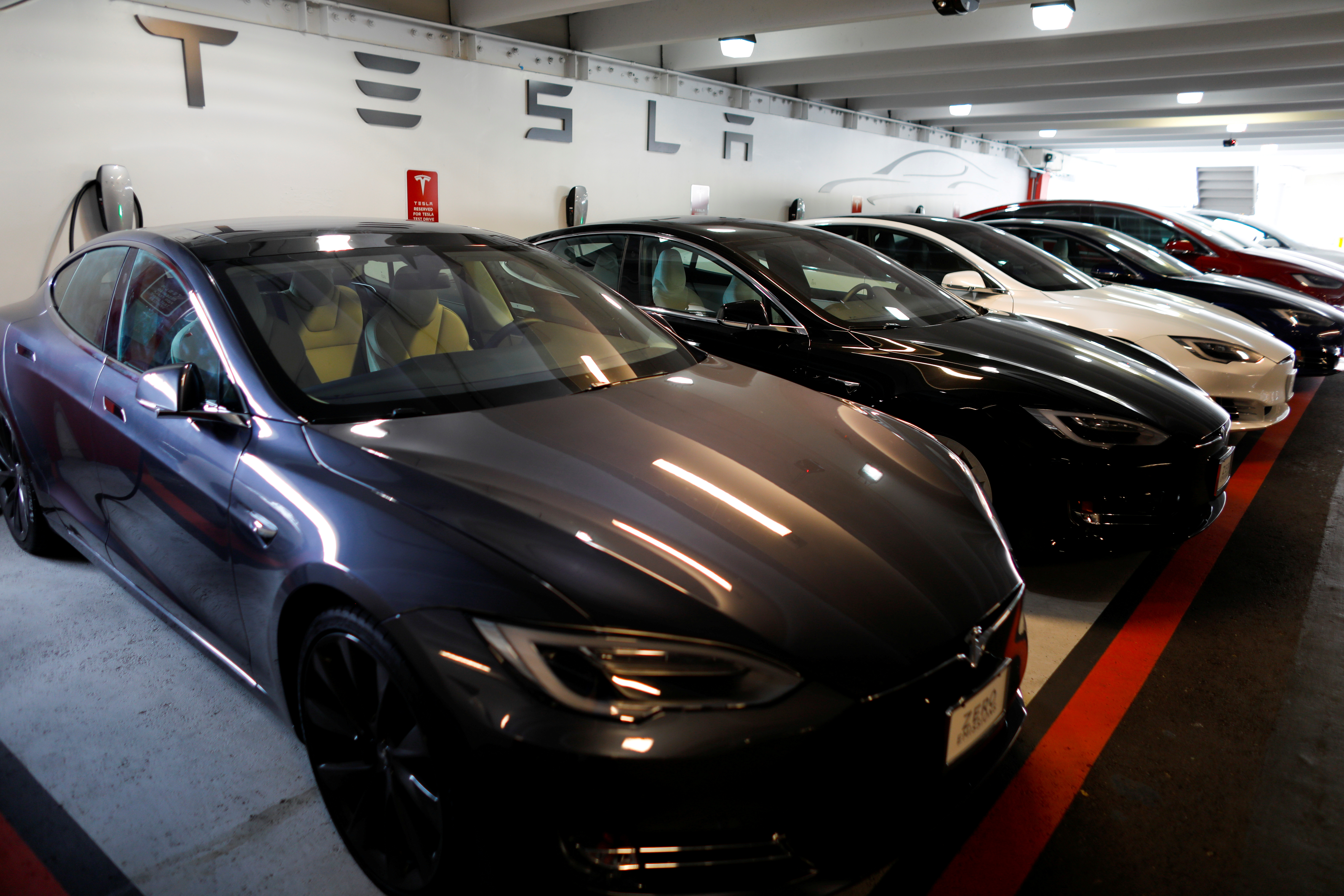 Tesla Model 3 and X cars charging in an underground parking lot next to a Tesla store in San Diego, California, U.S., May 30, 2018. REUTERS/Mike Blake