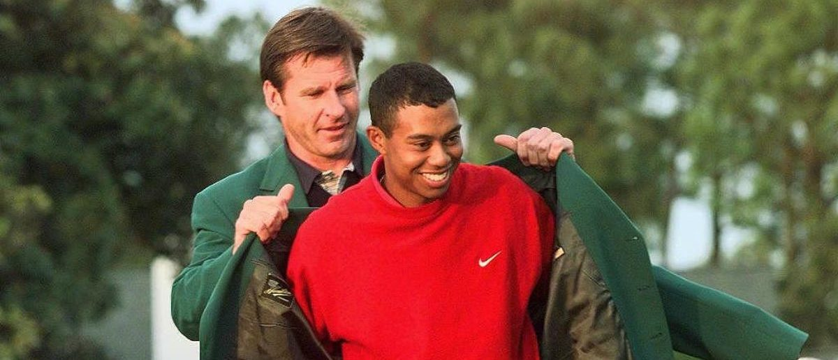 AUGUSTA, : Tiger Woods (R) receives the Masters green jacket for winning the 1997 Masters Tournament 13 April from 1996 winner Nick Faldo at Augusta National Golf Club in Georgia. Woods won the tournament with a record eighteen-under-par. (ELECTRONIC IMAGE) AFP PHOTO/Jeff HAYNES (Photo credit: JEFF HAYNES/AFP/Getty Images)