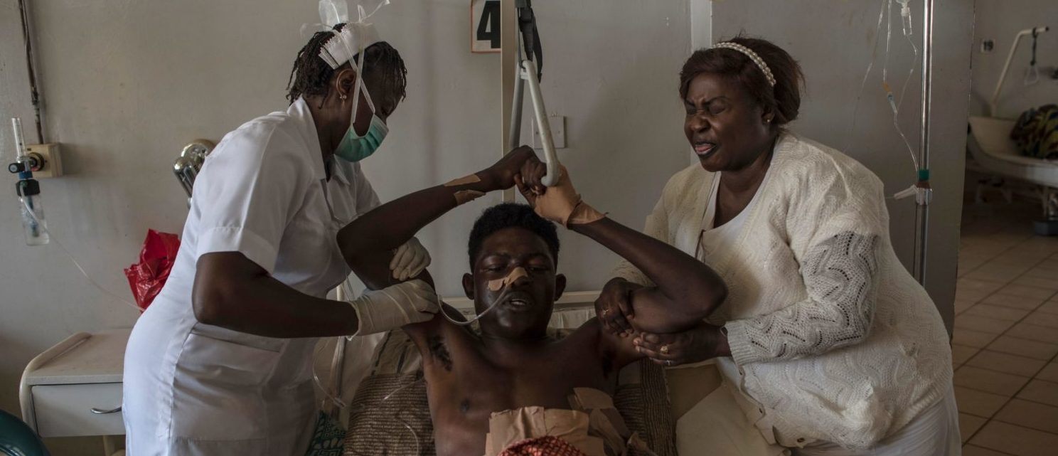 Nurses assist a man that sustained multiple stab wounds and machete cuts during the farmer-Fulani clashes to pull himself up at the Jos University Teaching Hospital on June 28, 2018. - Plateau State in Nigeria has seen days of violence where more than 200 people have been killed in clashes between Berom farmers and Fulani herders, Nigeria is facing an escalation in clashes between farmers and Fulani herders over land use and resources that is deepening along religious and ethnic lines. (STEFAN HEUNIS/AFP/Getty Images)