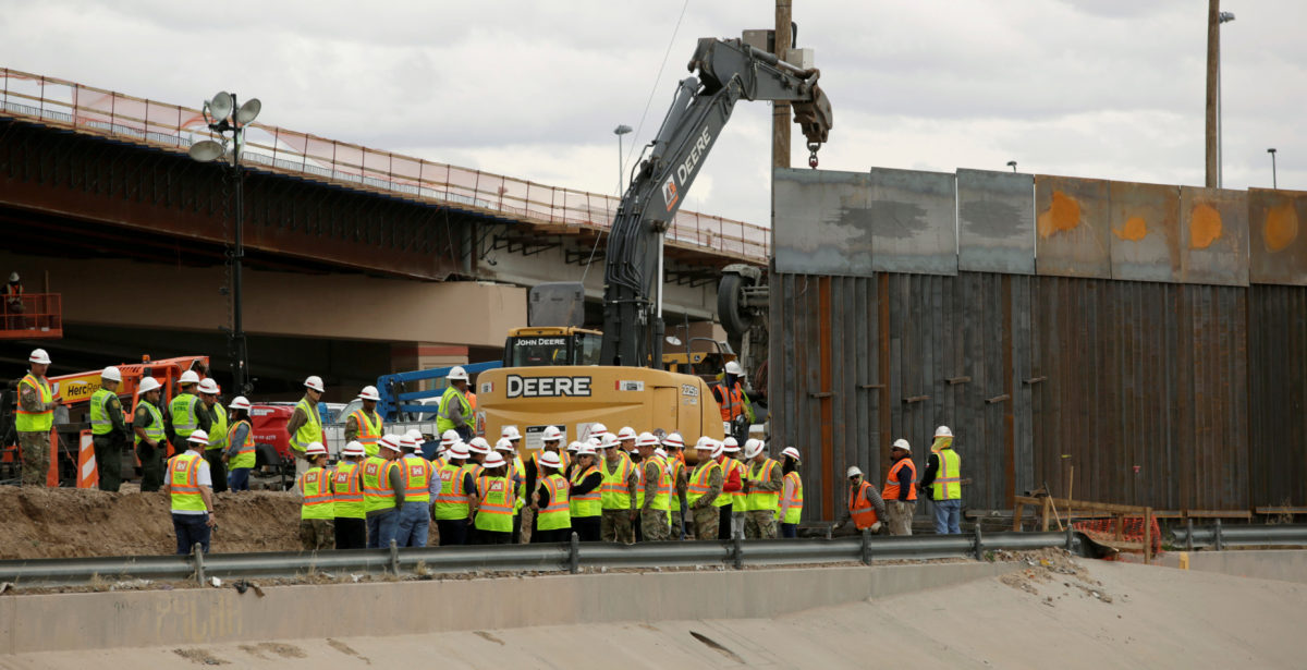 FILE PHOTO: Workers and U.S border patrol officers stand next to an excavator working in a section of the new wall between El Paso and Ciudad Juarez