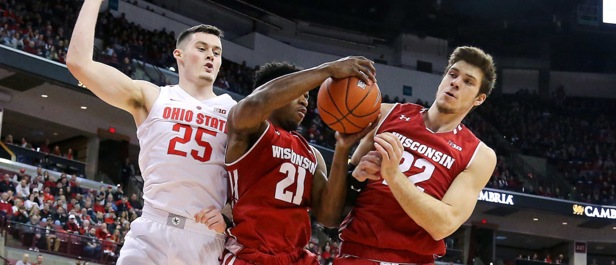 Mar 10, 2019; Columbus, OH, USA; Ohio State Buckeyes forward Kyle Young (25) battles for a rebound against Wisconsin Badgers guard Khalil Iverson (21) and forward Ethan Happ (22) during the first half at Value City Arena. (Mandatory Credit: Joe Maiorana-USA TODAY Sports - via Reuters)