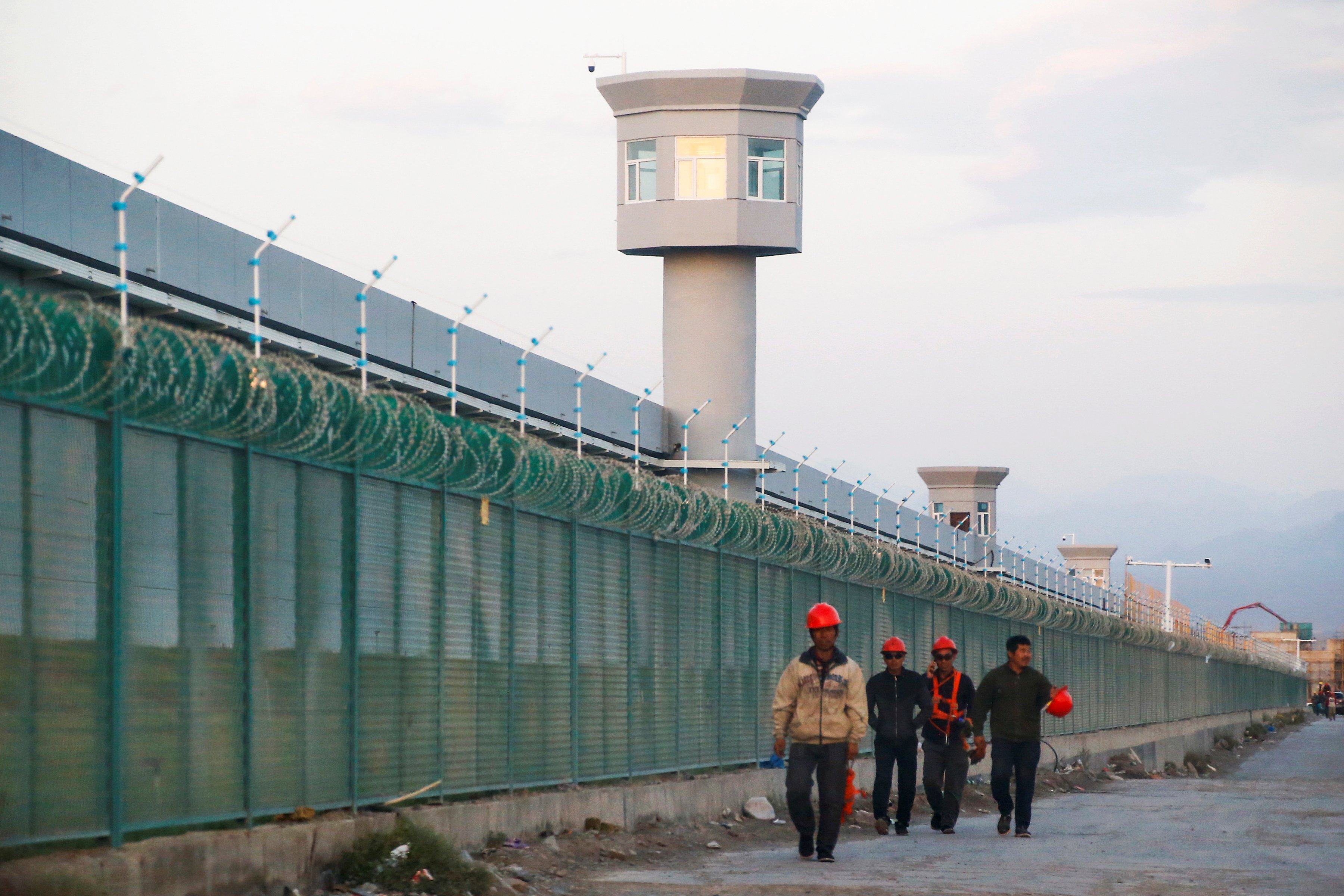 Workers walk by the perimeter fence of what is officially known as a vocational skills education centre in Dabancheng in Xinjiang Uighur Autonomous Region, China September 4, 2018. REUTERS/Thomas Peter