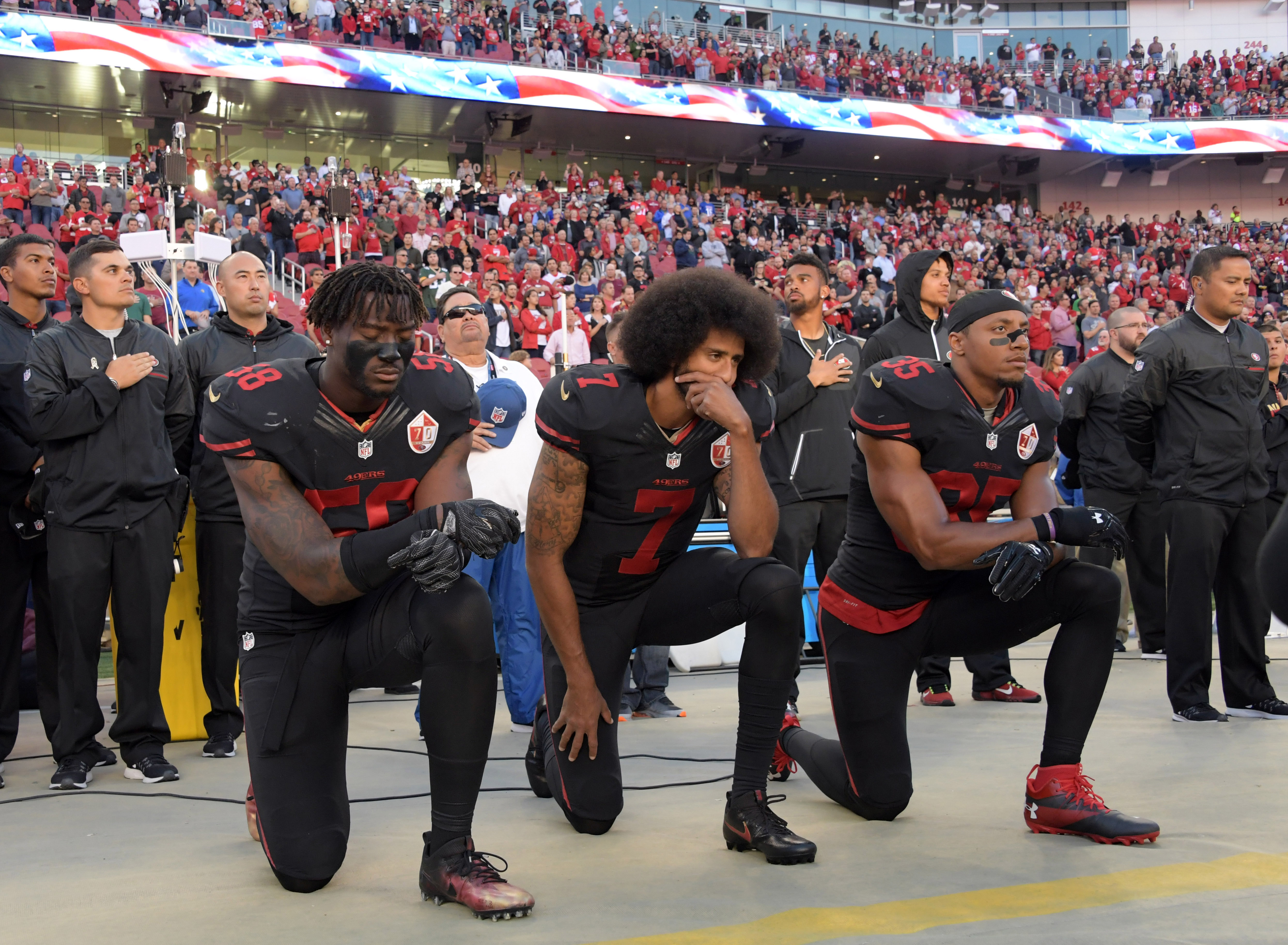 Oct 6, 2016; Santa Clara, CA, USA; San Francisco 49ers outside linebacker Eli Harold (58), quarterback Colin Kaepernick (7) and free safety Eric Reid (35) kneel in protest during the playing of the national anthem before a NFL game against the Arizona Cardinals at Levi's Stadium. Mandatory Credit: Kirby Lee-USA TODAY Sports/ Reuters