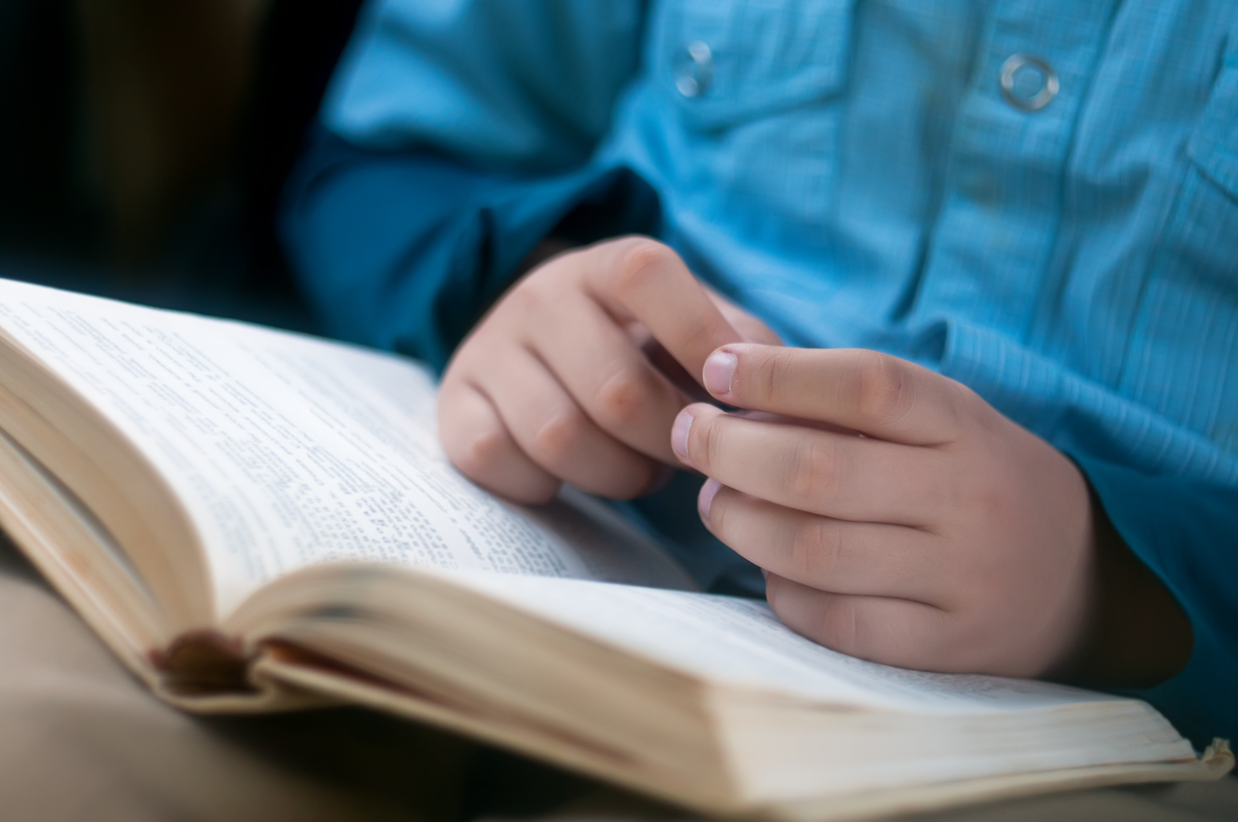 Child hands are on the open book (Yuliya Evstratenko/Shutterstock)