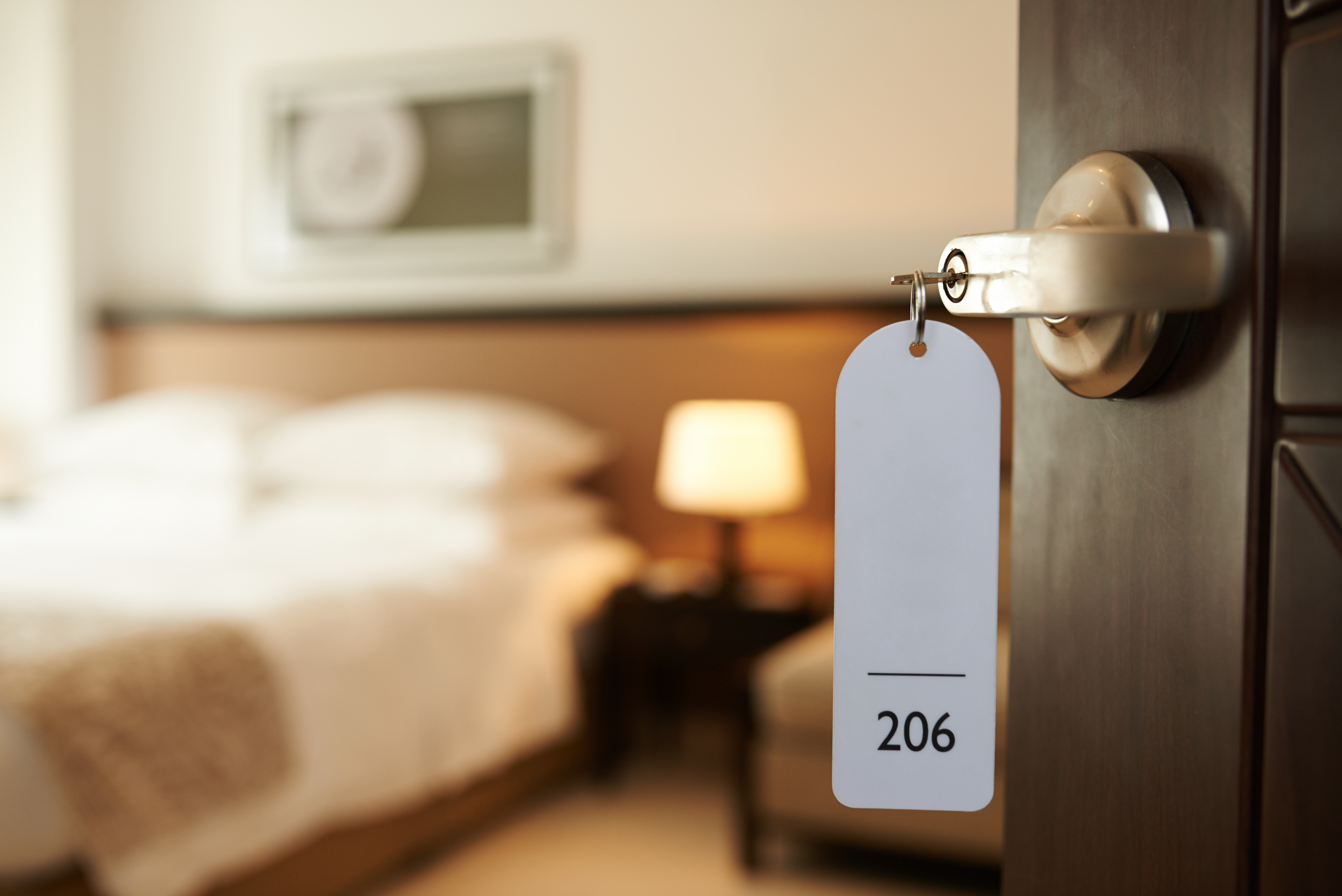 Opened door of hotel room with key in the lock. (Dragon Images/Shutterstock.com)