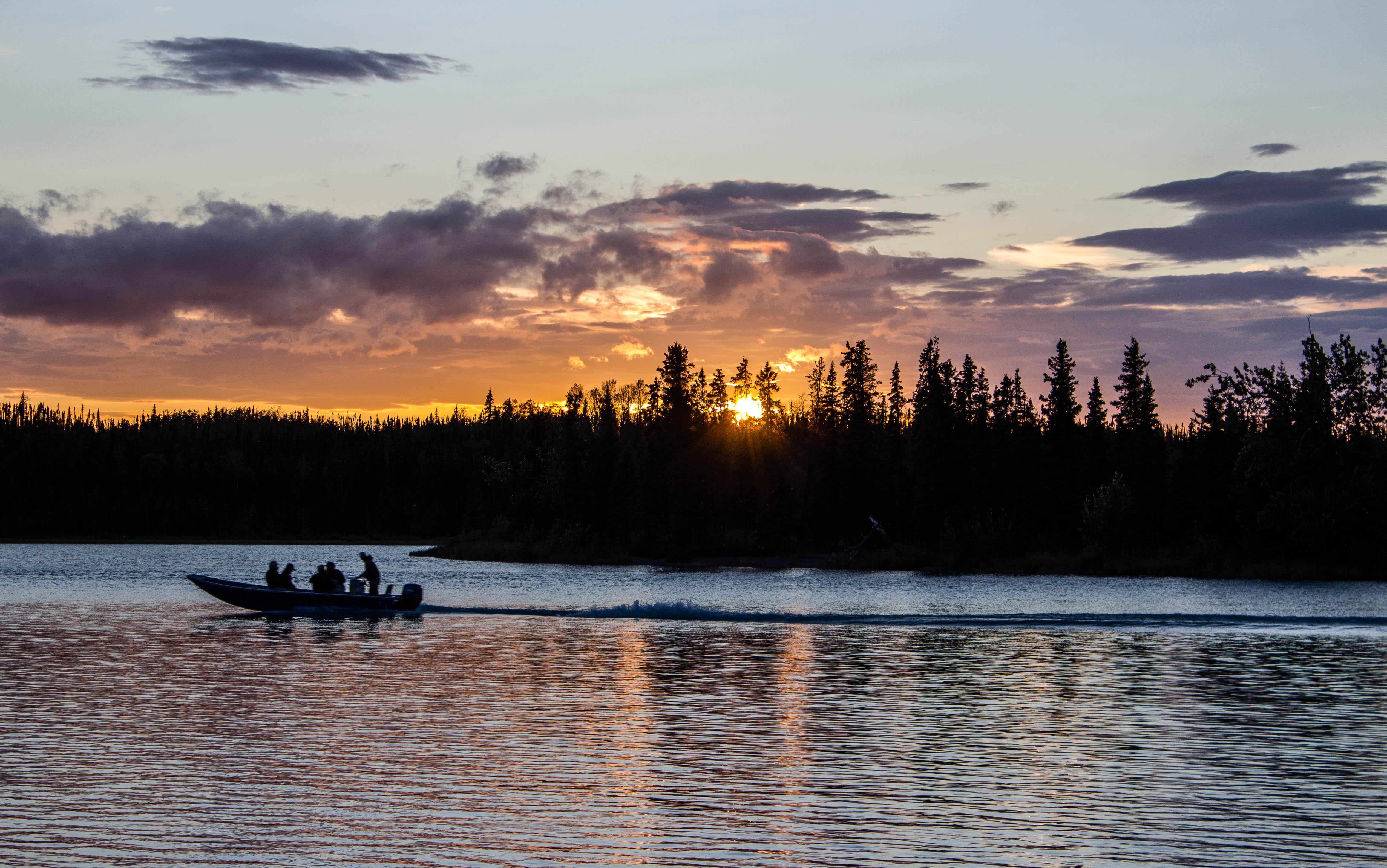 People go fishing at sunset along the Kenai River in Alaska. Shutterstock image via user Amber Walker