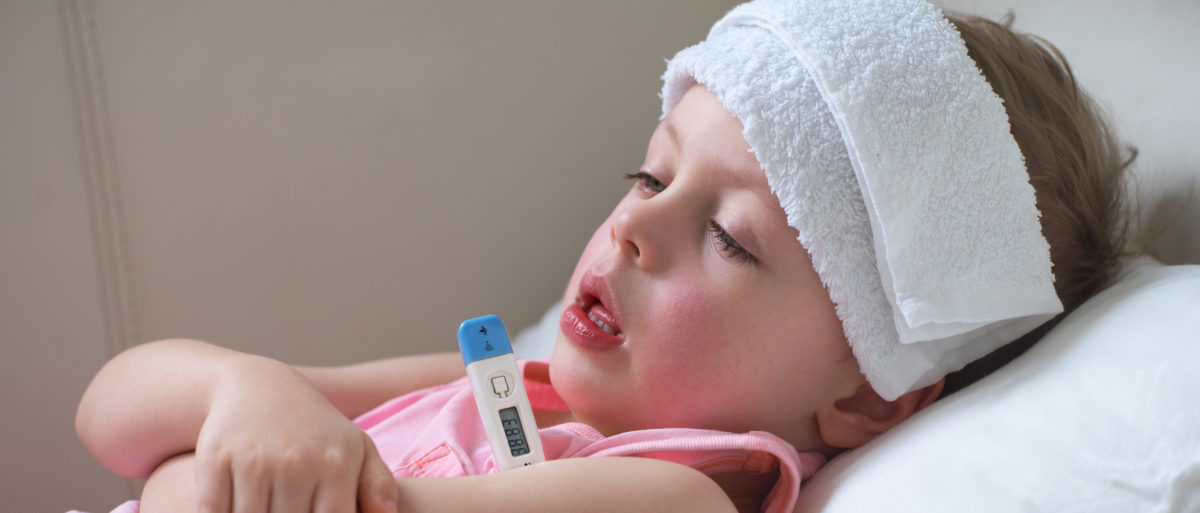 A sick child lays in bed. Shutterstock image via user Nataliya Petrovich