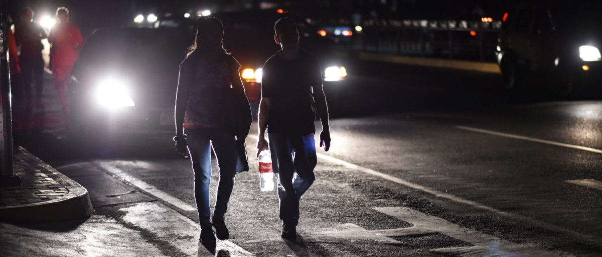 A couple walks along a street during a power cut in Caracas on March 7, 2019. (Photo credit should read YURI CORTEZ/AFP/Getty Images)