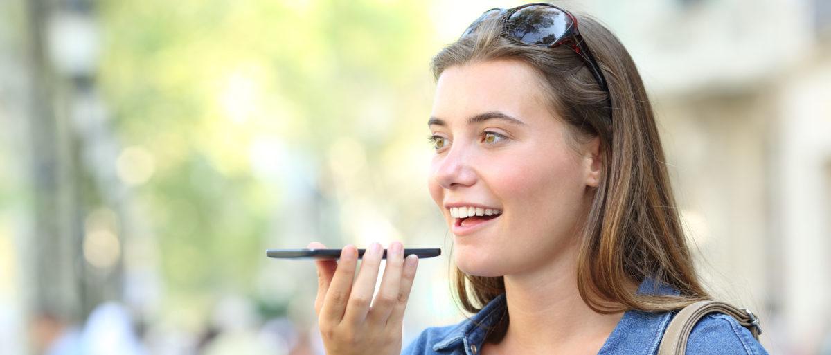 A woman speaks into her smartphone. Shutterstock image via user Antonio Guillem