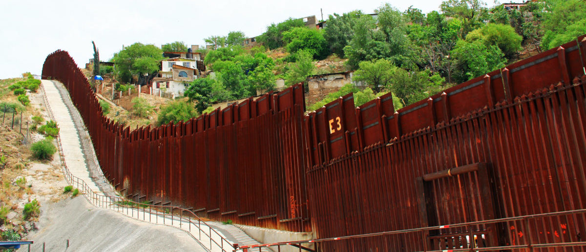 A border fence is pictured beside a street in downtown Nogales, Arizona, separating the United States from Mexico. Shutterstock