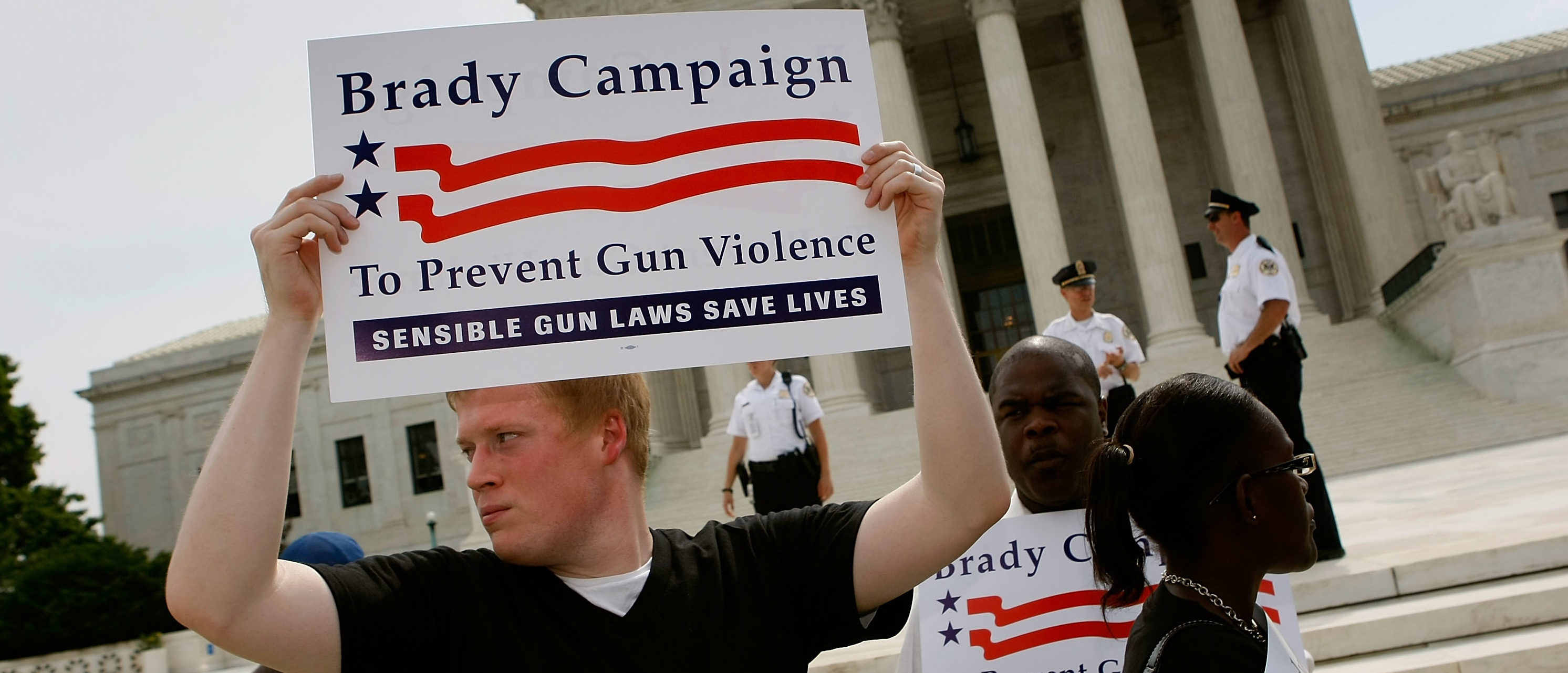 An activist with the Brady Campaign for gun control holds a sign as he stands in front stand in front of the U.S. Supreme Court' after the decision on the District of Columbia's gun ban was announced, June 26, 2008 in Washington DC. (Photo by Mark Wilson/Getty Images)
