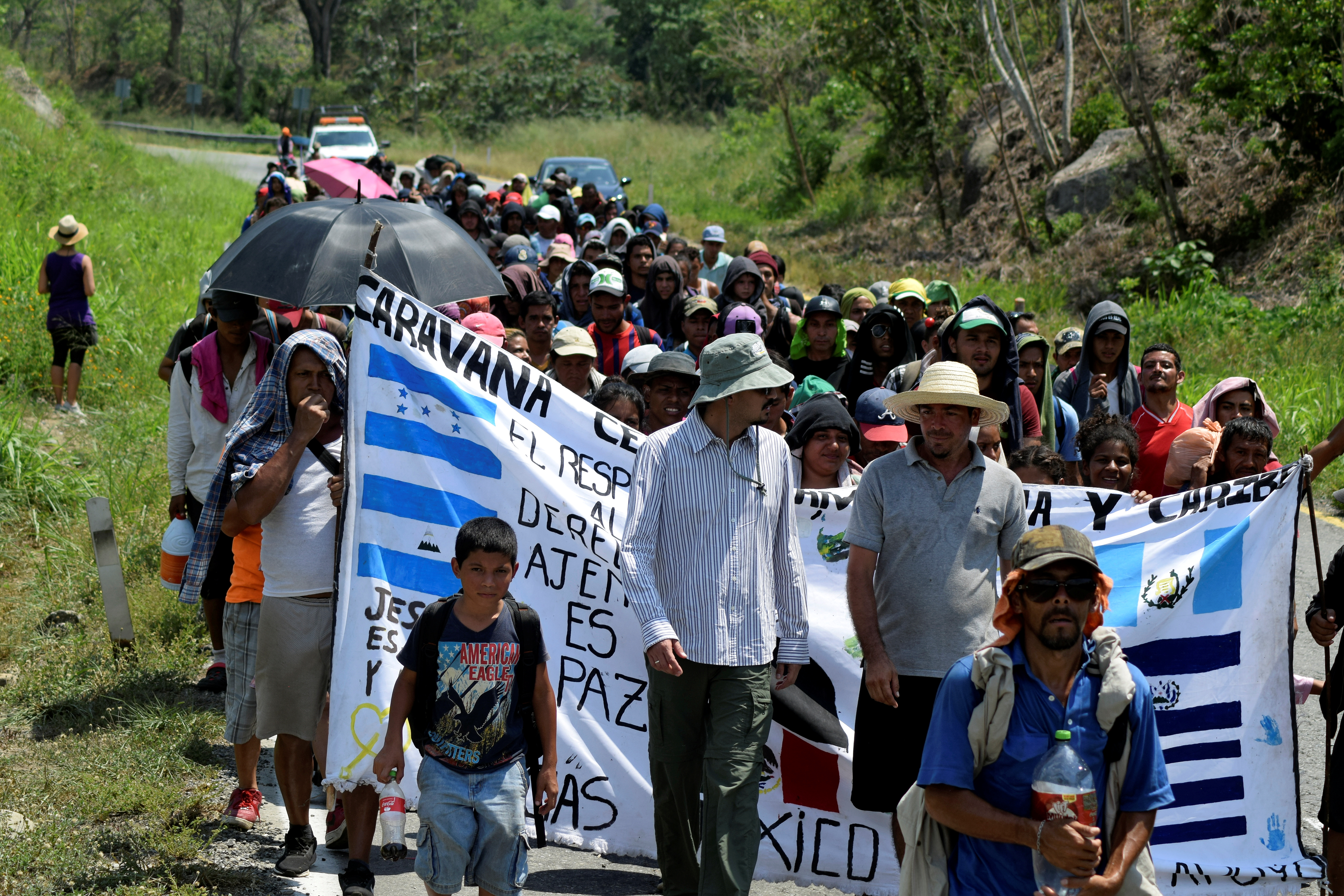 Migrants from Central America and Cuba walk on a highway during their journey towards the United States, in Escuintla
