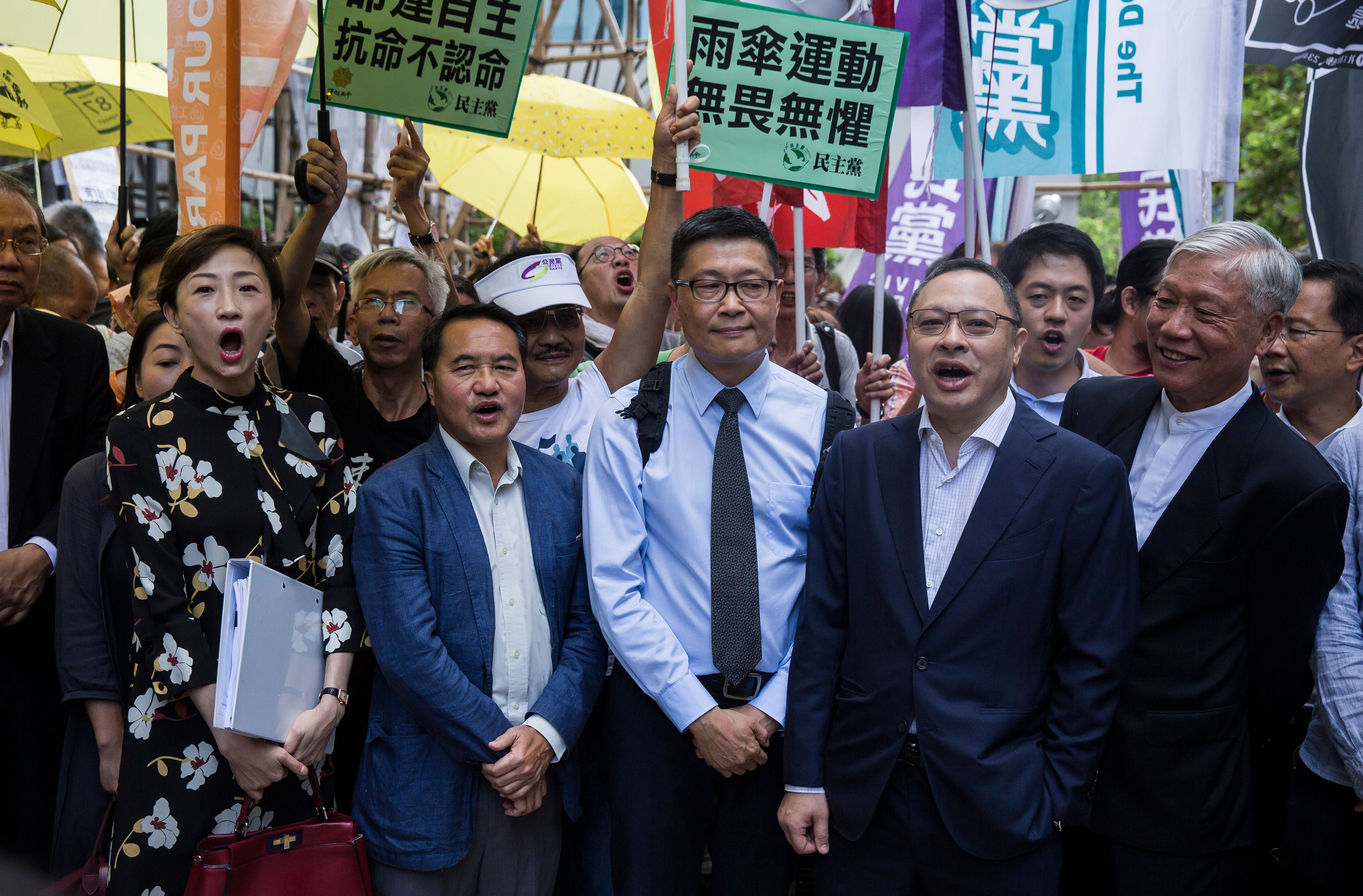 "(L to R) Tanya Chan, Lee Wing-tat, Chan Kin-mam, Benny Tai and Chu Yiu-ming chant slogans in front of the District Court before the trial on public nuisance charges of some of the leaders of the ""Umbrella Movement"" rallies in 2014 calling for democratic reforms in Hong Kong on September 19, 2017. (ISAAC LAWRENCE/AFP/Getty Images)"
