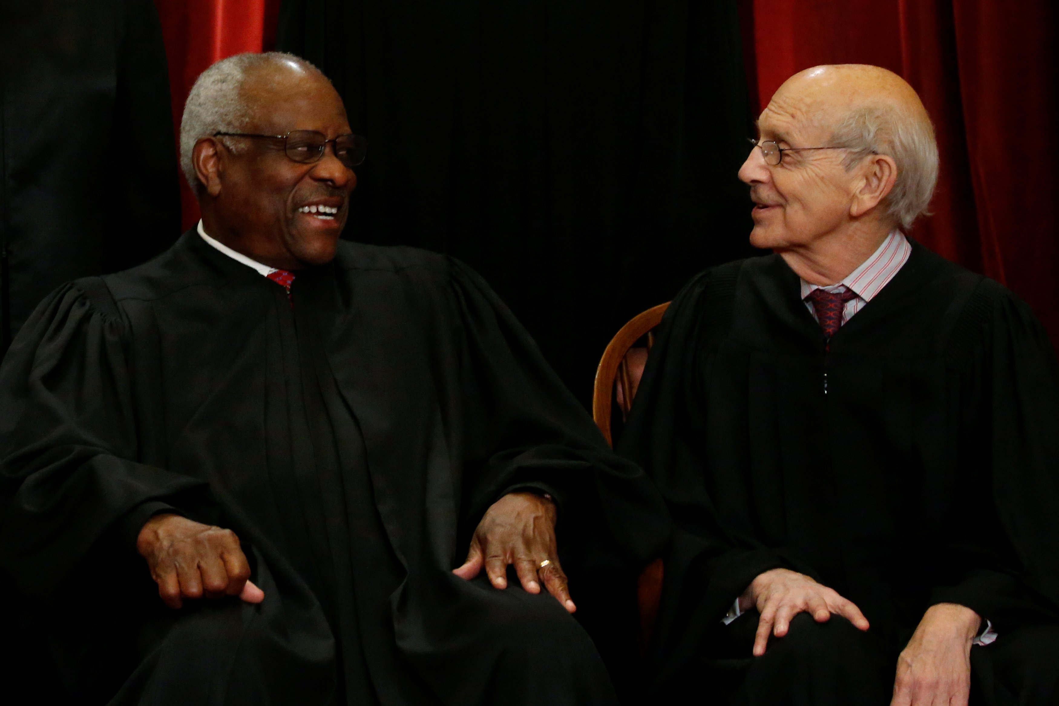 Justice Clarence Thomas (L) and Justice Stephen Breyer chat during a new Supreme Court family photo including on June 1, 2017. REUTERS/Jonathan Ernst