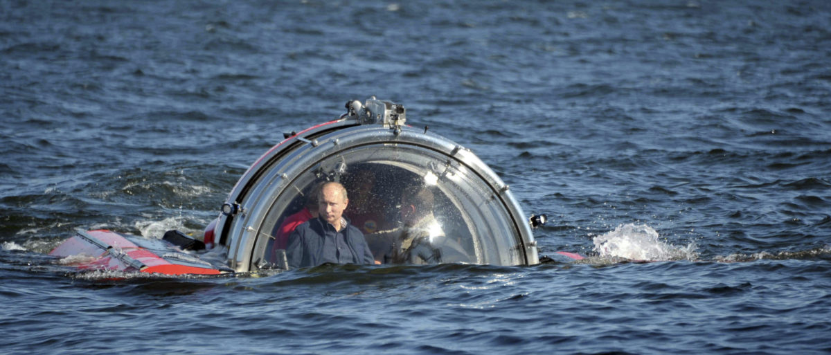 "Russia's President Vladimir Putin (L) is seen through the glass of C-Explorer 5 submersible after a dive to see the remains of the naval frigate ""Oleg"", which sank in the 19th century, in the Gulf of Finland in the Baltic Sea July 15, 2013. REUTERS/Aleksey Nikolskyi/RIA Novosti/Kremlin"
