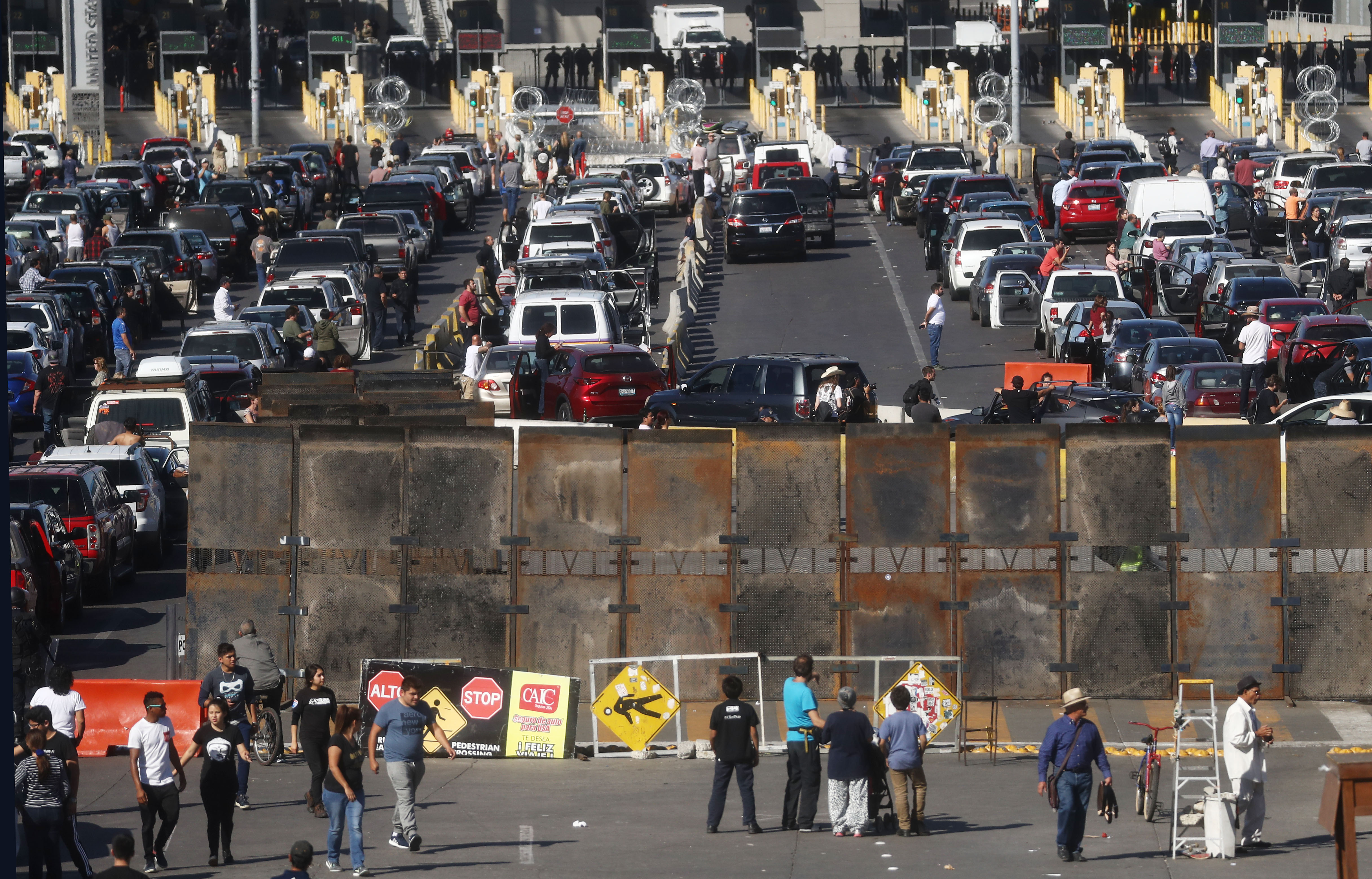 People attempting to cross in the U.S. look on as the San Ysidro port of entry stands closed at the U.S.-Mexico border on November 25, 2018 in Tijuana, Mexico. Migrants circumvented a police blockade as they attempted to approach the El Chaparral port of entry and U.S. Customs and Border Protection temporarily closed the two ports of entry on the border with Tijuana in response. Around 6,000 migrants from Central America have arrived in the city with the mayor of Tijuana declaring the situation a 'humanitarian crisis'. (Photo by Mario Tama/Getty Images)