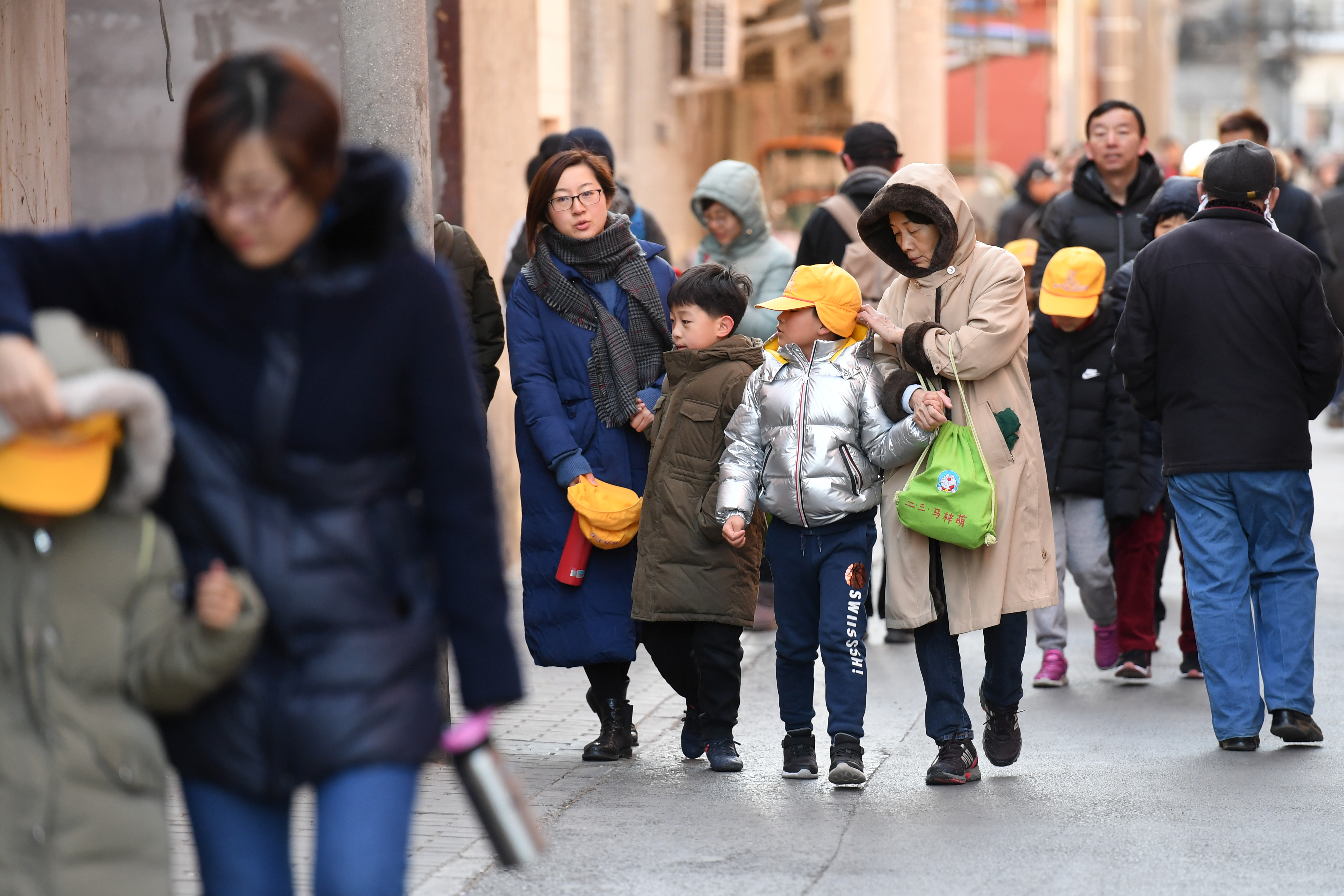 Parents and family members escort their children just outside the gates of an elementary school in Beijing following an attack on January 8, 2019. (GREG BAKER/AFP/Getty Images)