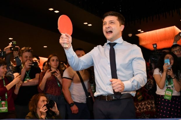 Ukrainian comic actor, showman and presidential frontrunner Volodymyr Zelensky surrounded by cameramen and photographers plays table tennis with a journalist ahead of the provisional results at the headquarter in Kiev on March 31, 2019. (GENYA SAVILOV/AFP/Getty Images)