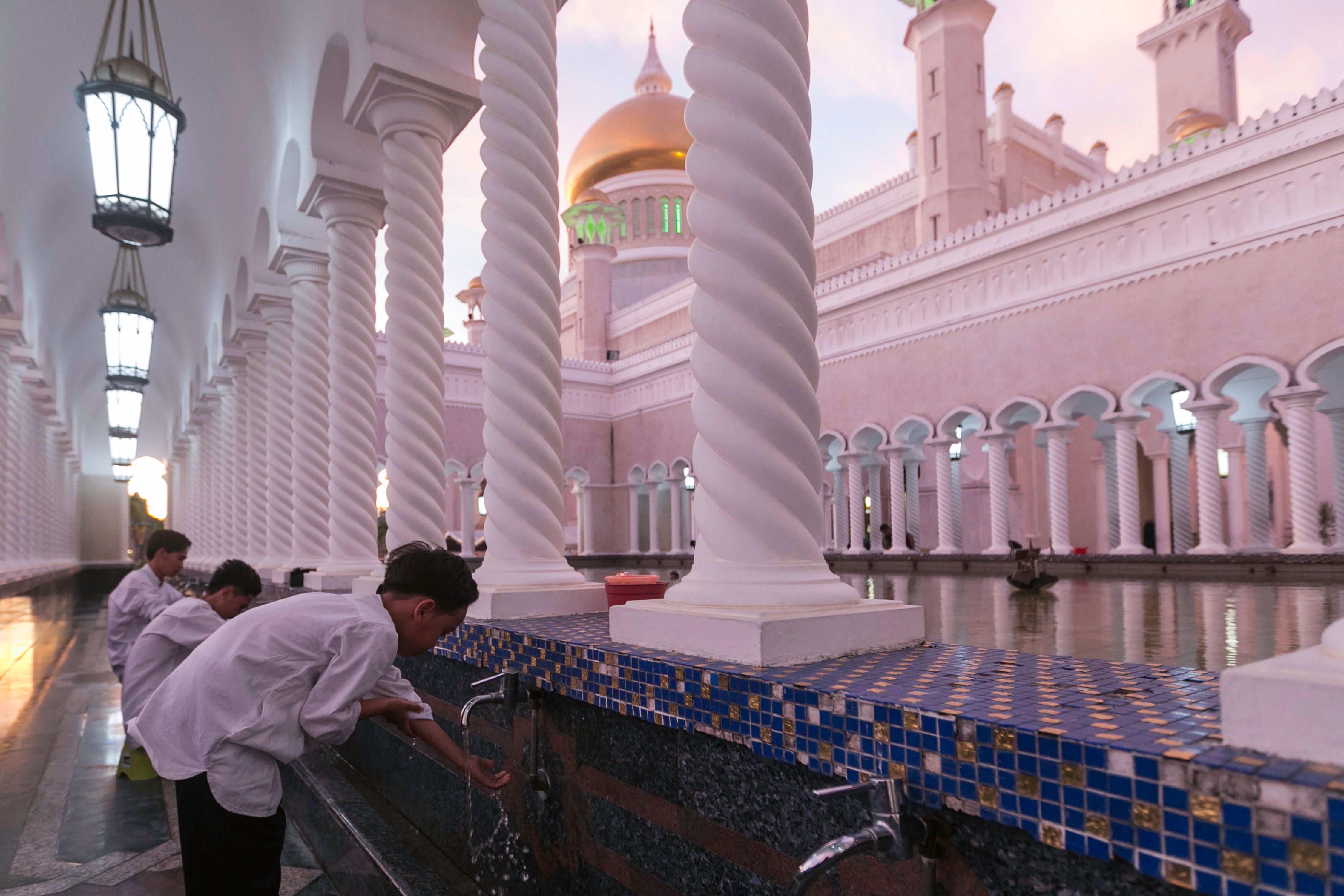 "In this picture taken on April 1, 2019 children perform ablution before praying at the Sultan Omar Ali Saifuddien mosque in Bandar Seri Begawan. - The United Nations decried on April 1 new ""cruel and inhuman"" laws set to take effect in Brunei this week which impose death by stoning for gay sex and adultery, and amputations for theft. (Photo by - / AFP) / Brunei OUT (Photo credit should read -/AFP/Getty Images)"