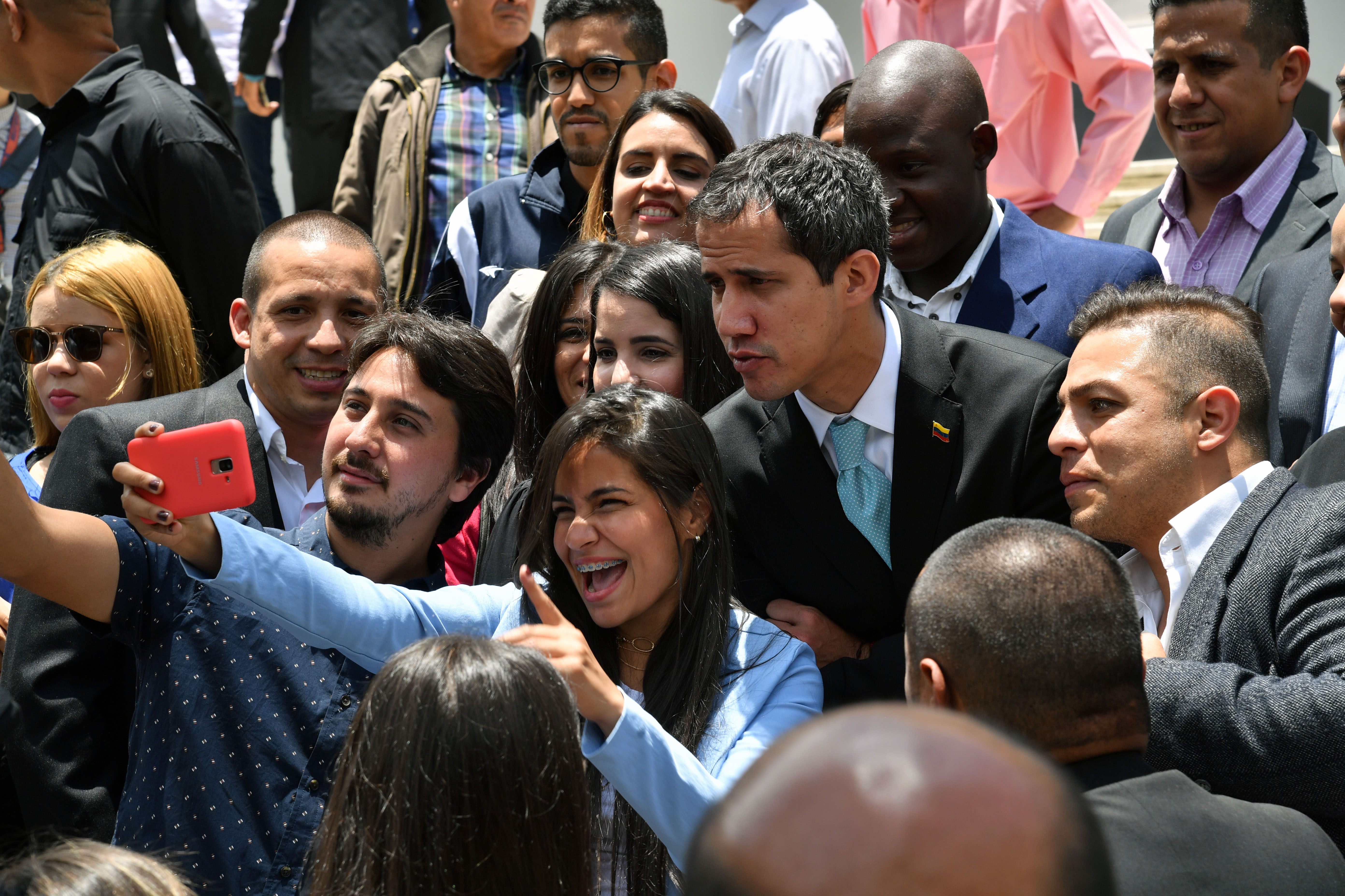 "Juan Guaido (C), the speaker of the Venezuelan opposition-controlled National Assembly who declared himself interim president in January, poses for a selfie with supporters after attending the ""Meeting with Young Leaders for Venezuela"", at the Federal Legislative Palace in Caracas on April 4, 2019. (YURI CORTEZ/AFP/Getty Images)"