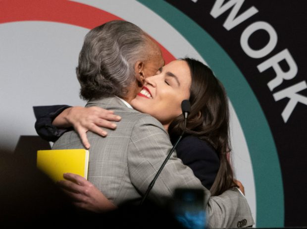 US Representative Alexandria Ocasio-Cortez (R) is welcomed by the Reverend Al Sharpton speaks during a gathering of the National Action Network April 5, 2019 in New York. (Photo by Don Emmert / AFP) (Photo credit should read DON EMMERT/AFP/Getty Images)