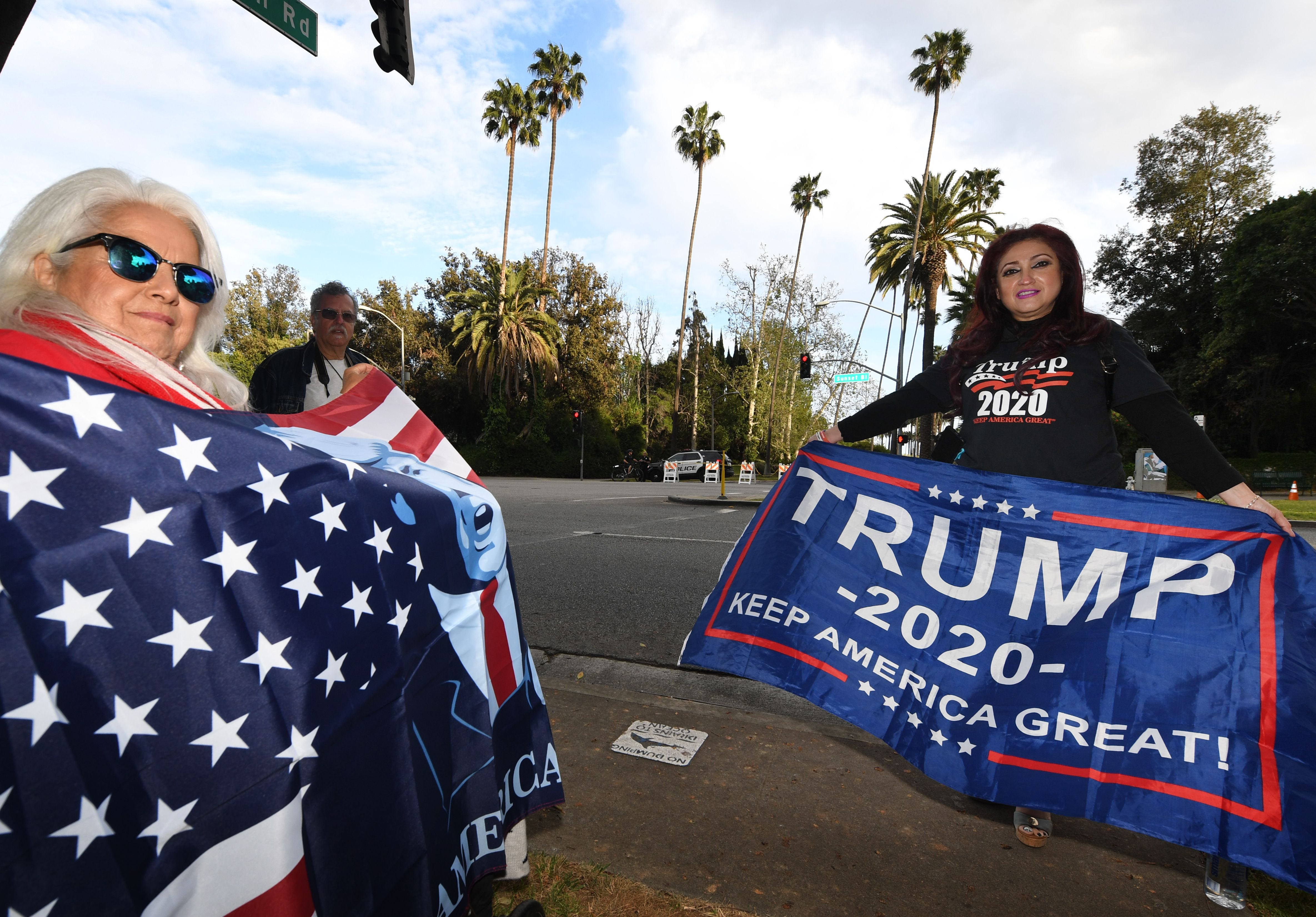 "Trump supporters pose for photos on Sunset Blvd as the US president attends a fundraiser nearby, in Beverly Hills, California, on April 5, 2019. - US President Donald Trump visited the Mexican border on April 5 to deliver a message to would-be illegal immigrants and asylum seekers: don't bother coming. ""The system is full and we can't take you anymore... Our country is full,"" he said at a meeting with border patrol officers and other officials in Calexico, California. ""So turn around, that's the way it is."" (Photo by Mark RALSTON / AFP) (Photo credit should read MARK RALSTON/AFP/Getty Images)"