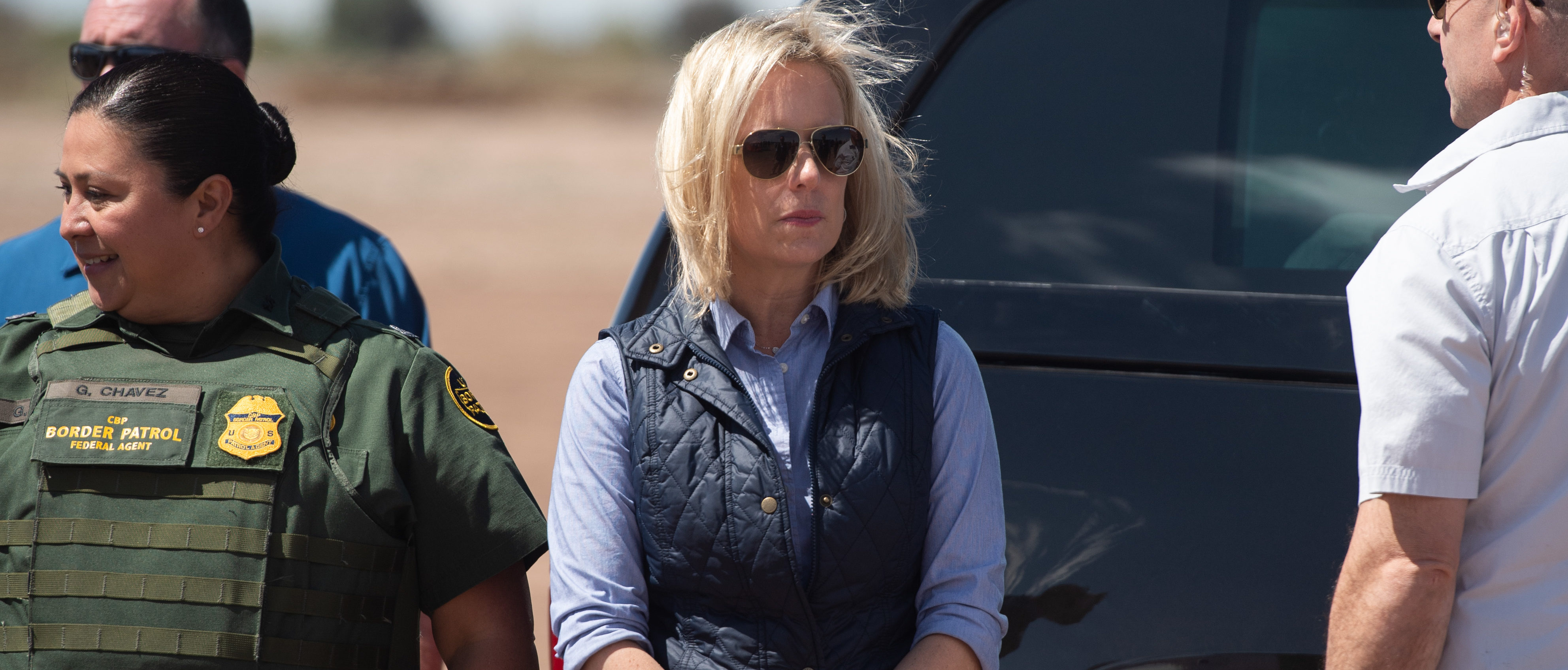 "In this photo taken on April 5, 2019, Secretary of Homeland Security Kirstjen Nielsen waits for US President Donald Trump as he arrives to tour the border wall between the United States and Mexico in Calexico, California. - US President Donald Trump on Sunday, April 7, 2019 announced Homeland Security Secretary Kirstjen Nielsen, the front-line defender of the administration's controversial immigration policies, would leave her position. ""Secretary of Homeland Security Kirstjen Nielsen will be leaving her position, and I would like to thank her for her service,"" Trump tweeted. He added US Customs and Border Protection Commissioner Kevin McAleenan would become acting secretary. (Photo by SAUL LOEB / AFP) (Photo credit should read SAUL LOEB/AFP/Getty Images)"